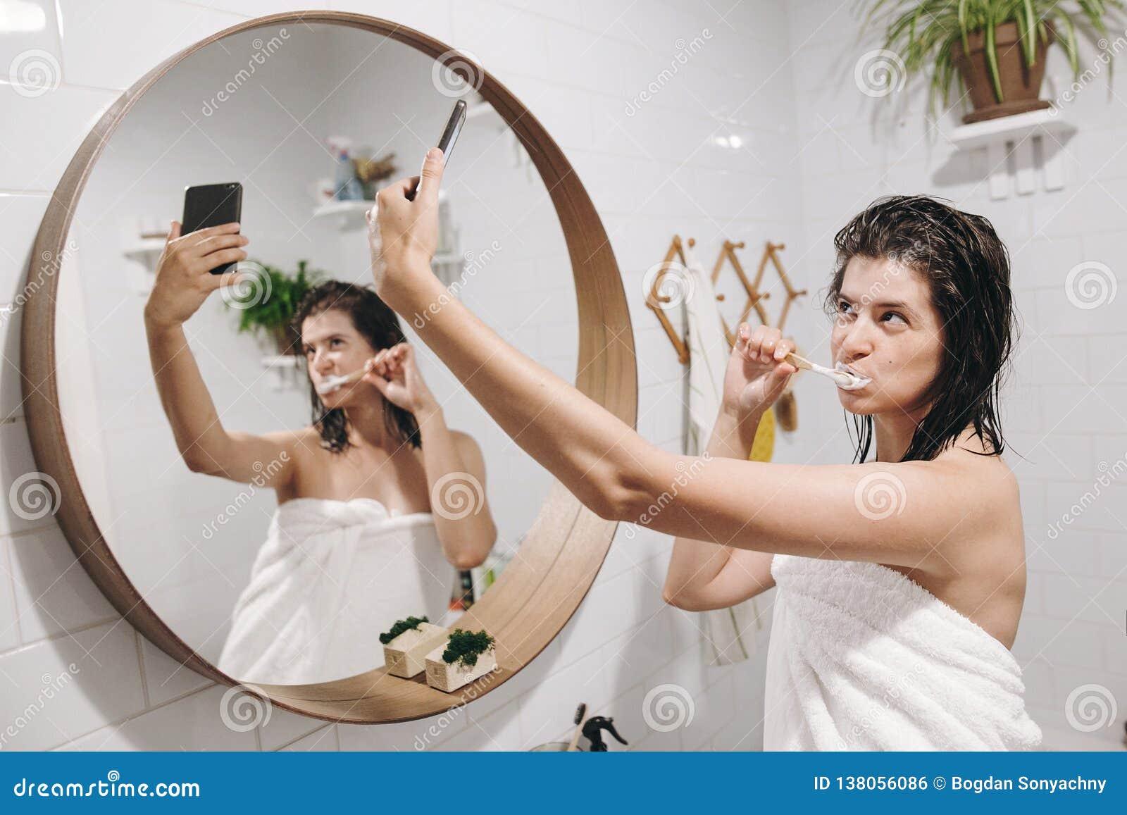 Os meios sociais afetam Mulher feliz nova na toalha branca que faz o selfie ao escovar os dentes e ao olhar o telefone no banheir