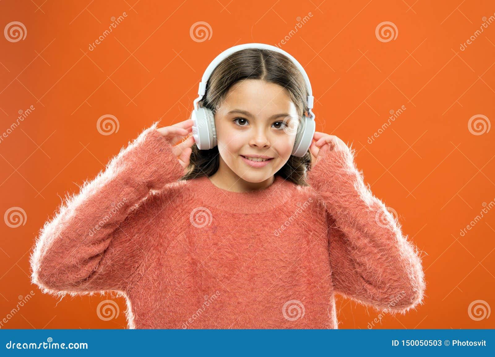 Os melhores apps livres da música para seu dispositivo móvel Aprecie o som A crian?a pequena bonito da menina veste fones de ouvi