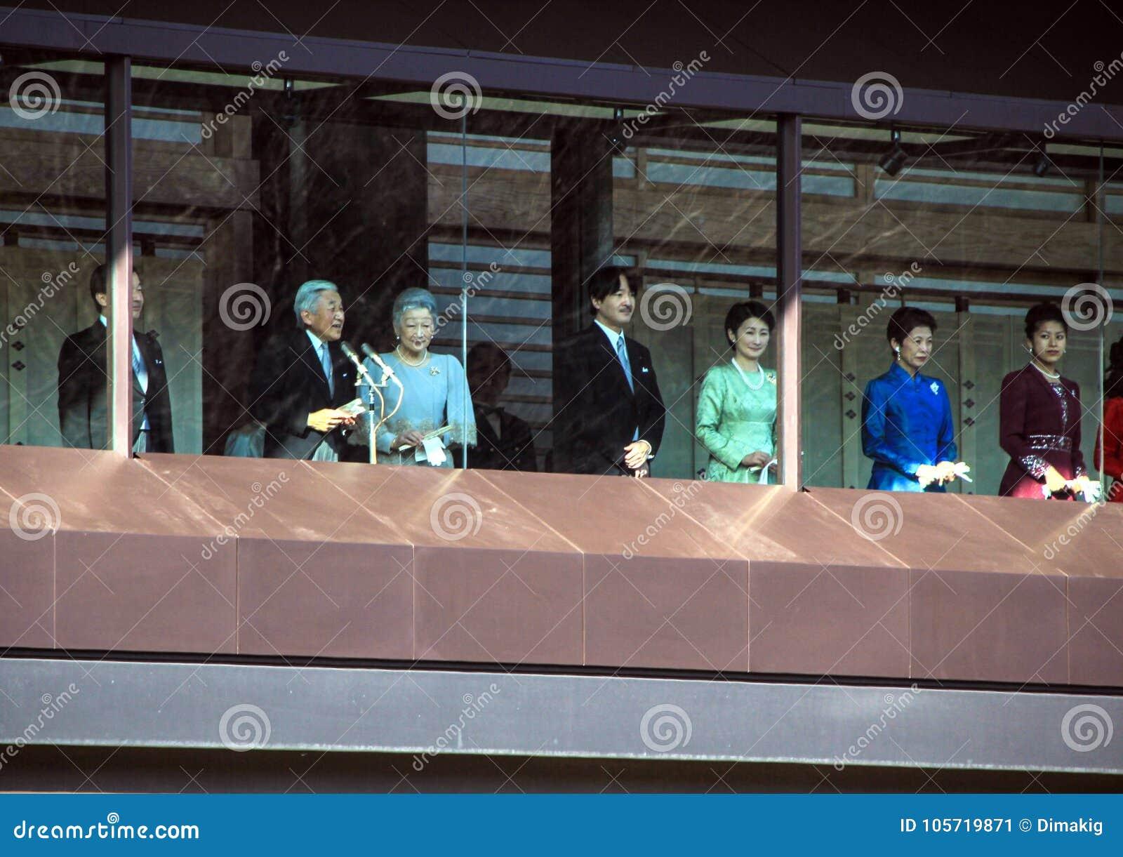 Os membros da família imperial no balcão do palácio são cumprimentados pelos povos no quadrado no Tóquio
