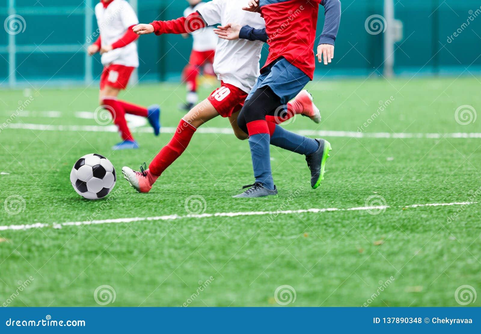 Os meninos no sportswear vermelho e branco jogam o futebol no campo de grama verde Jogo de futebol da juventude Competição de esp