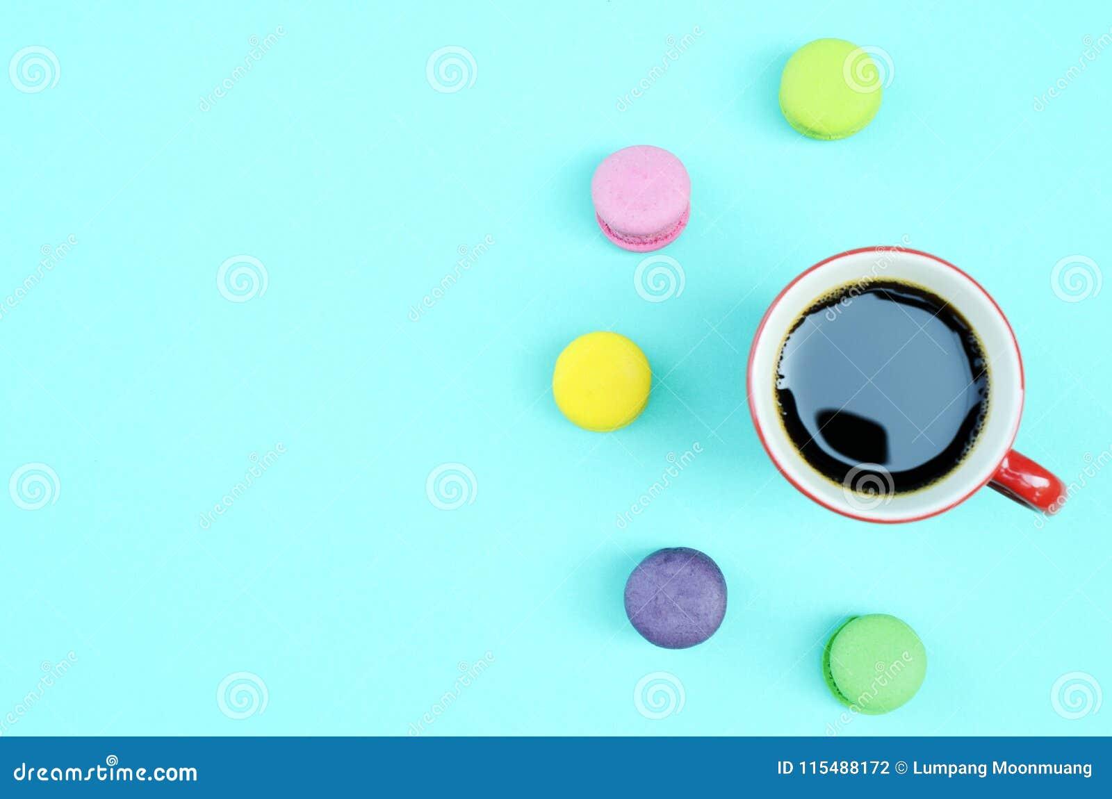 Os mini bolinhos de amêndoa e os copos vermelhos do café preto no azul iluminam o backgrou
