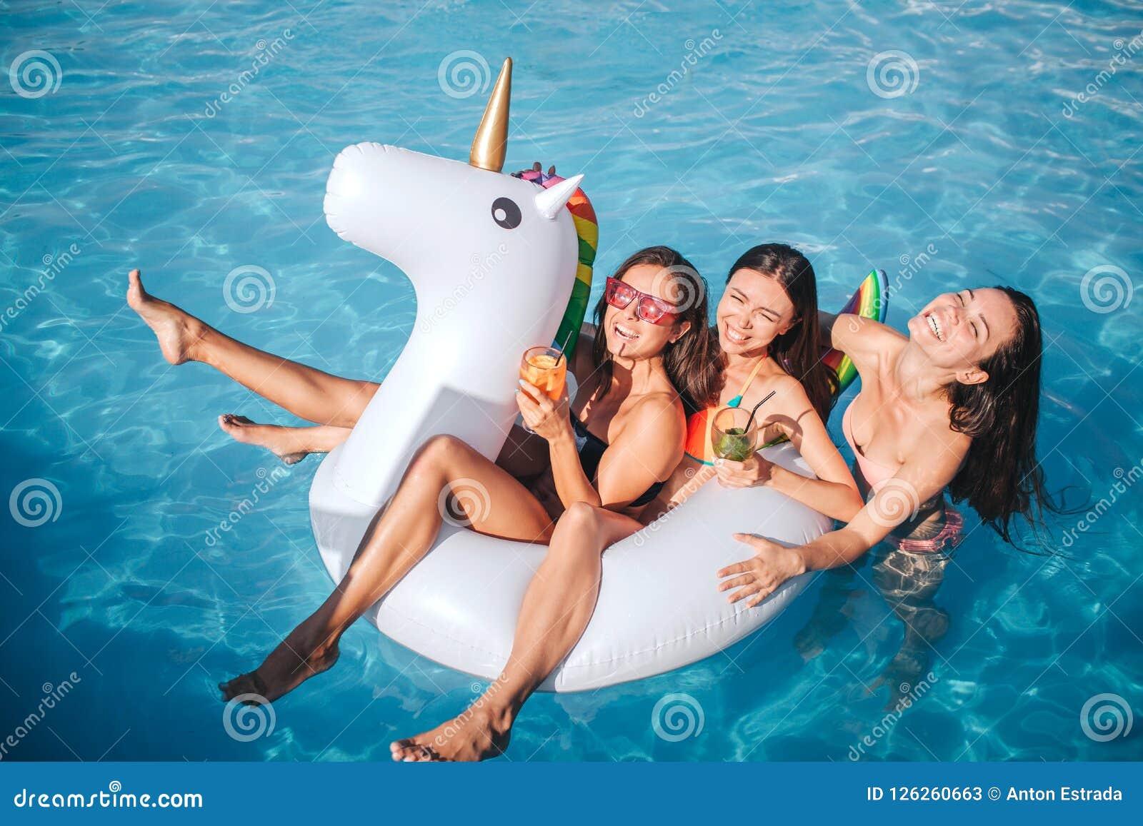 Os modelos atrativos estão na piscina Têm cocktail nas mãos Dois modelos sentam-se no flutuador Terceiro um que nada atrás