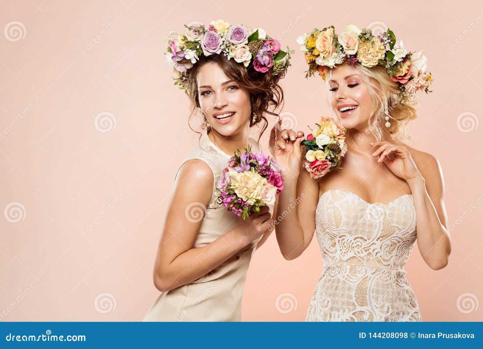 Os modelos de forma florescem o retrato da beleza do penteado, duas mulheres felizes com grinalda da flor e ramalhete