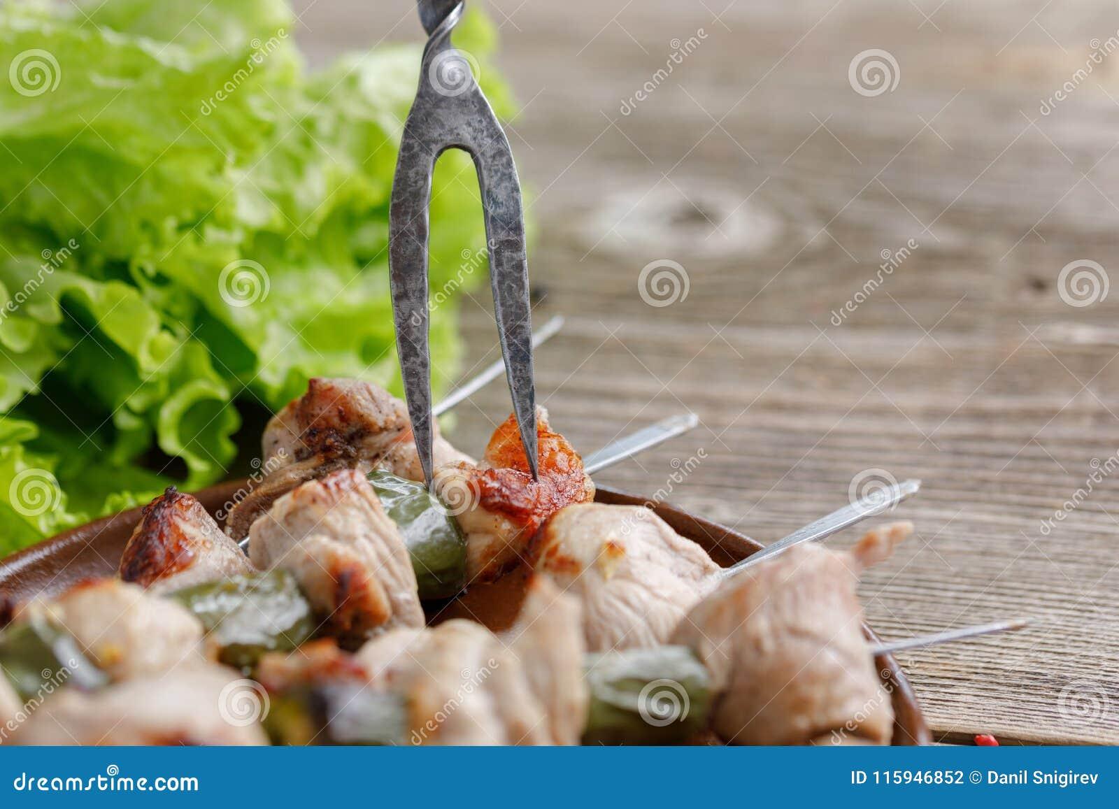 Os no espeto delicados da carne de porco cozinhados em um fogo aberto com uma forquilha excelente colaram neles ainda vida em um