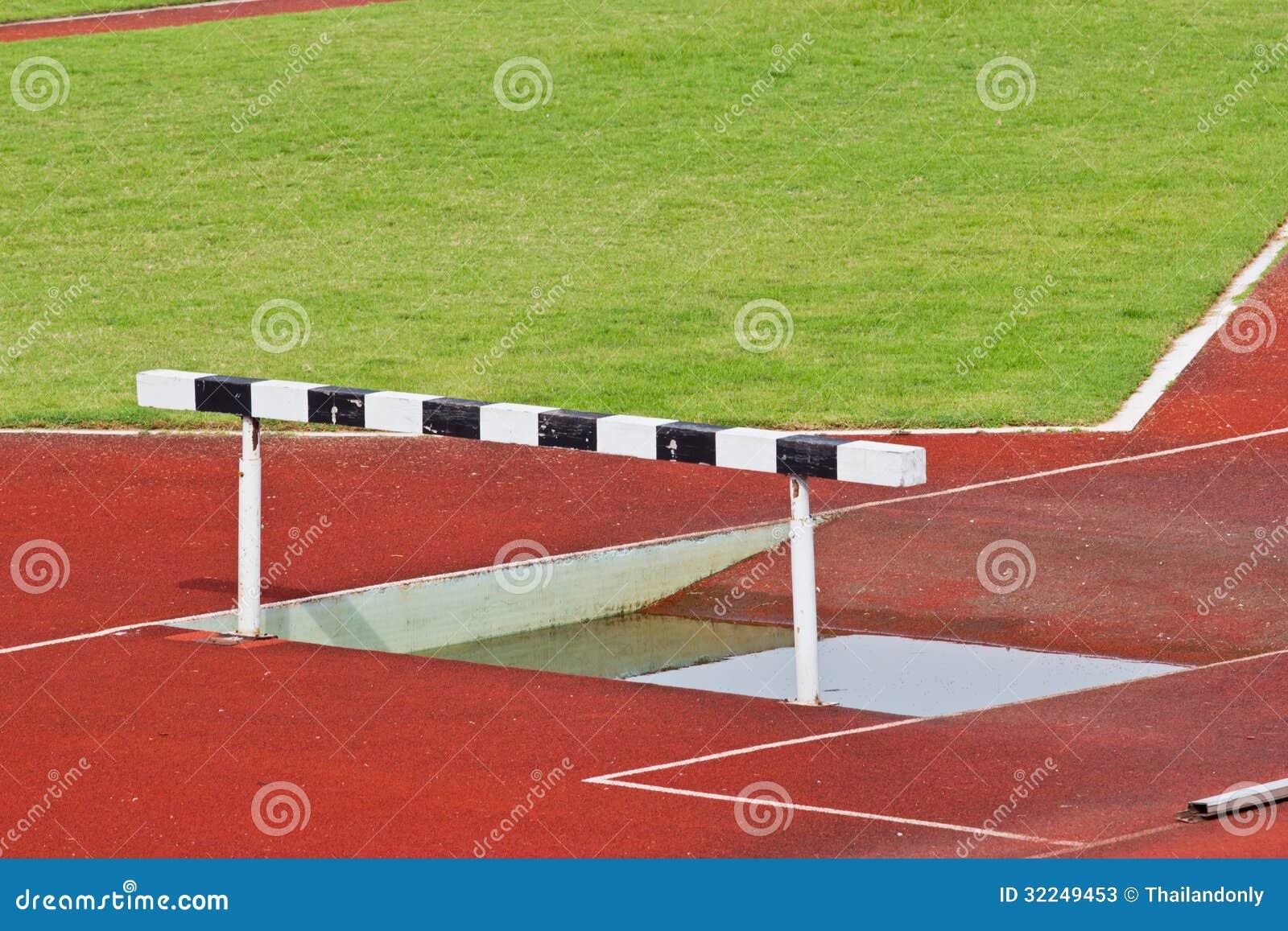 Os obstáculos na pista de atletismo vermelha prepararam-se para a competição.