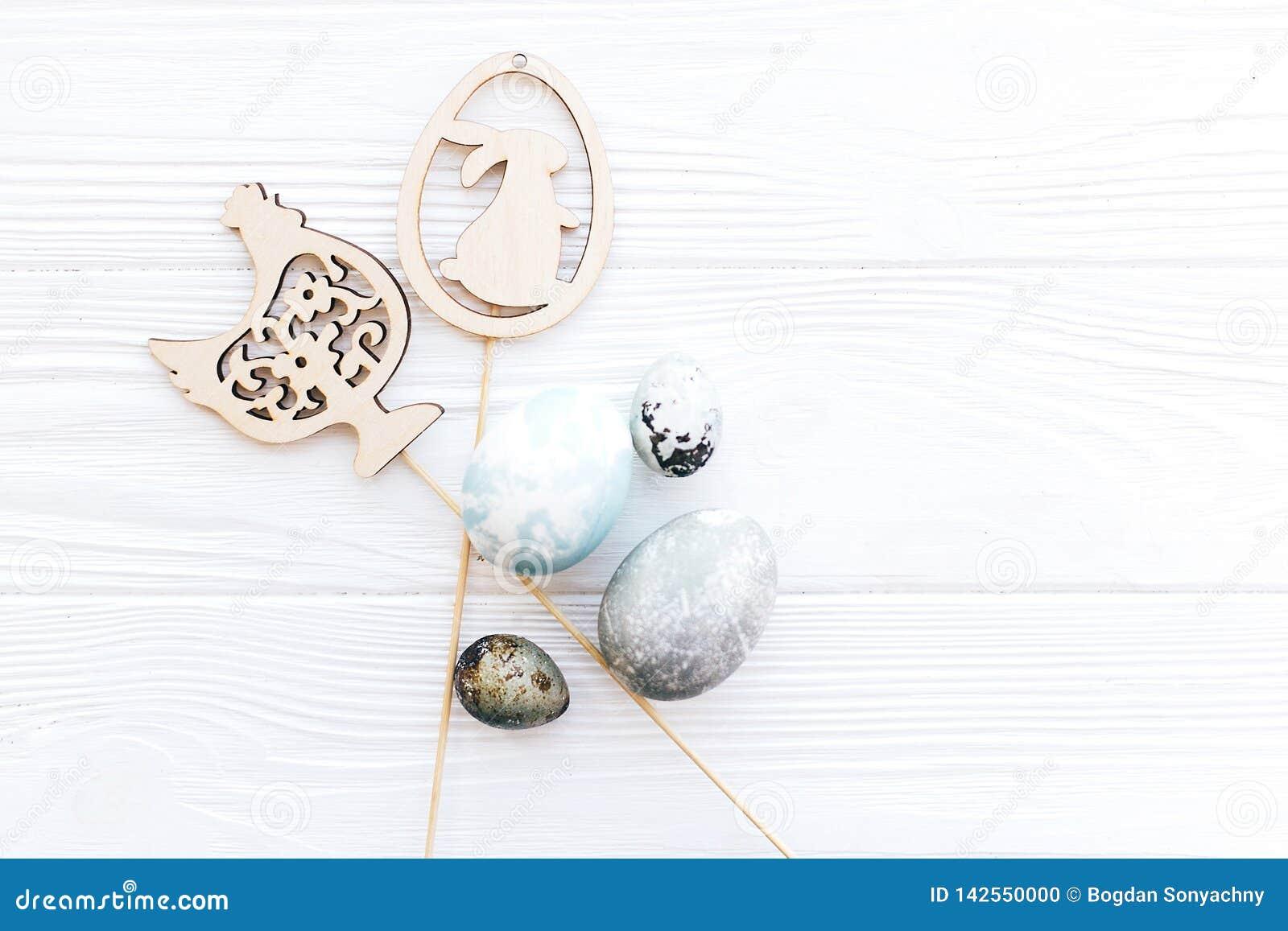 Os ovos da páscoa à moda e as decorações de madeira simples do coelho e da galinha no fundo de madeira branco, plano colocam com