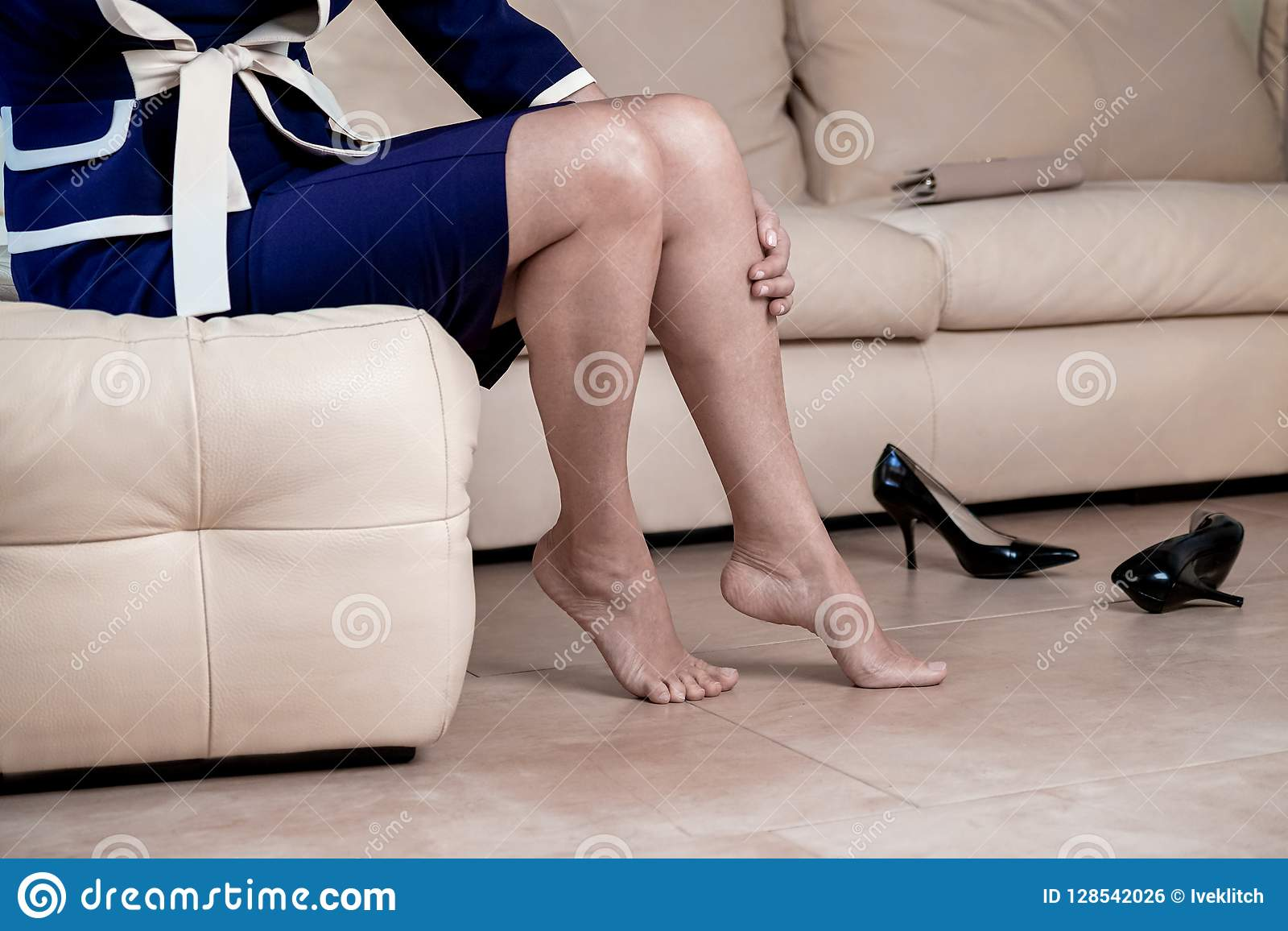 Os pés colhidos do ` s da mulher da opinião inferior do retrato que vestem o azul e o branco vestem as sapatas pretas do salto al