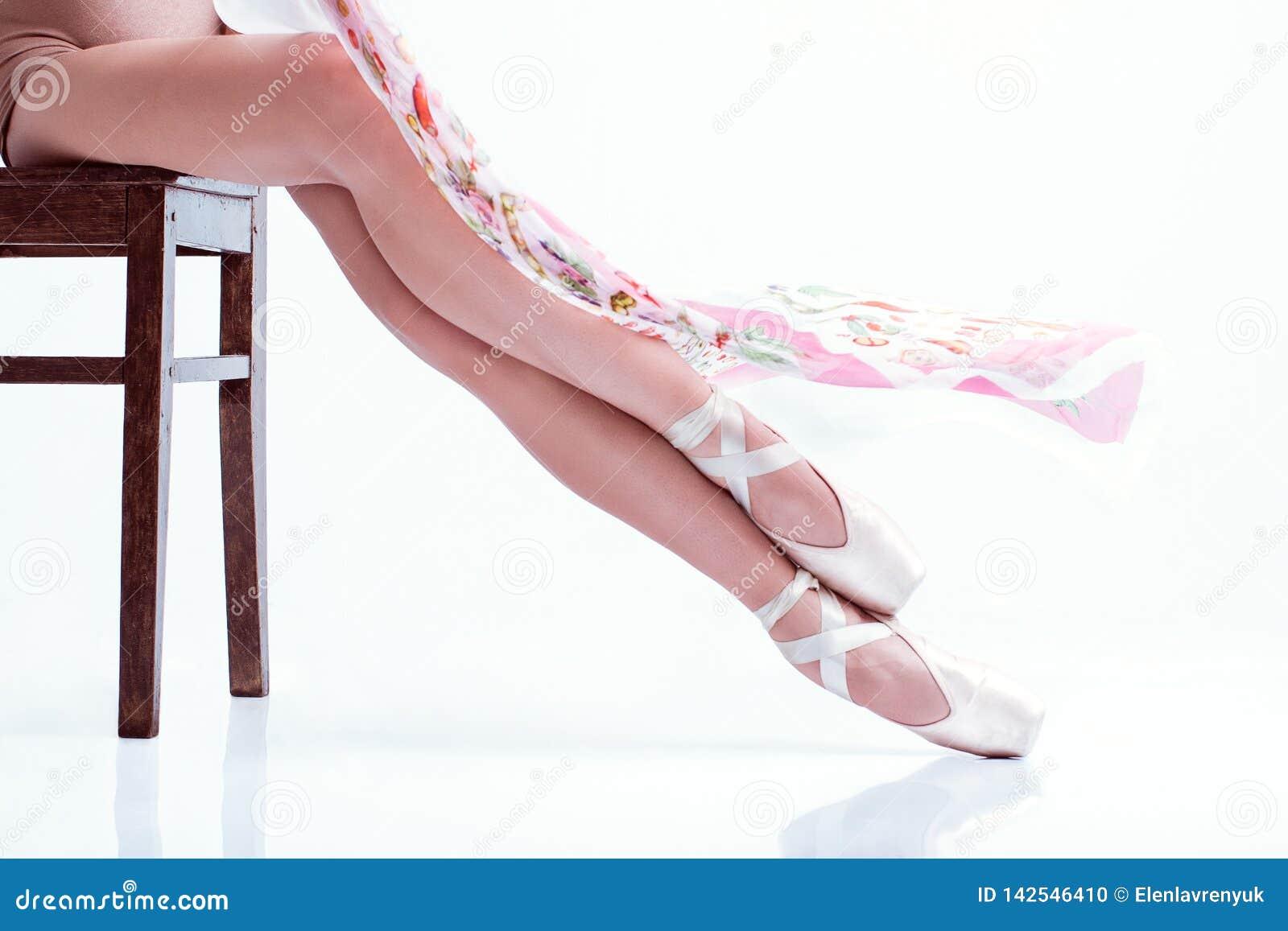 Os pés da bailarina no pointe e com o lenço de seda no fundo branco