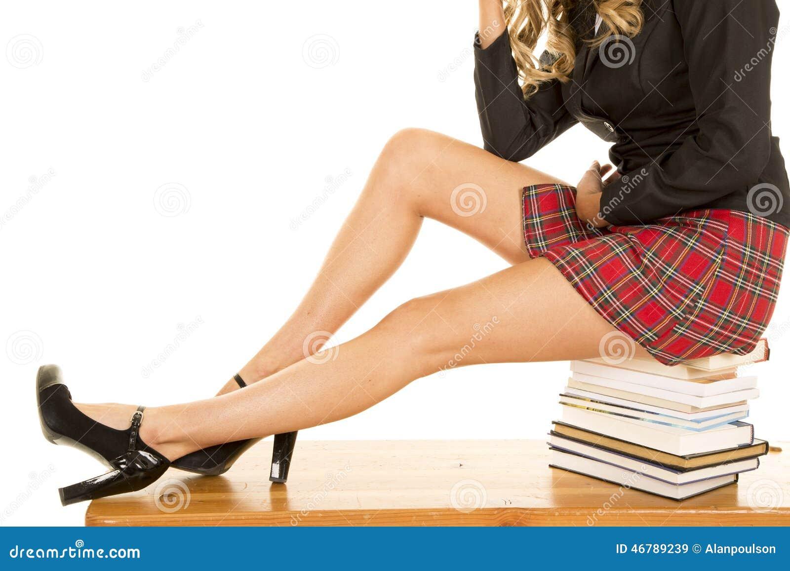 Os pés da menina da escola sentam-se em livros