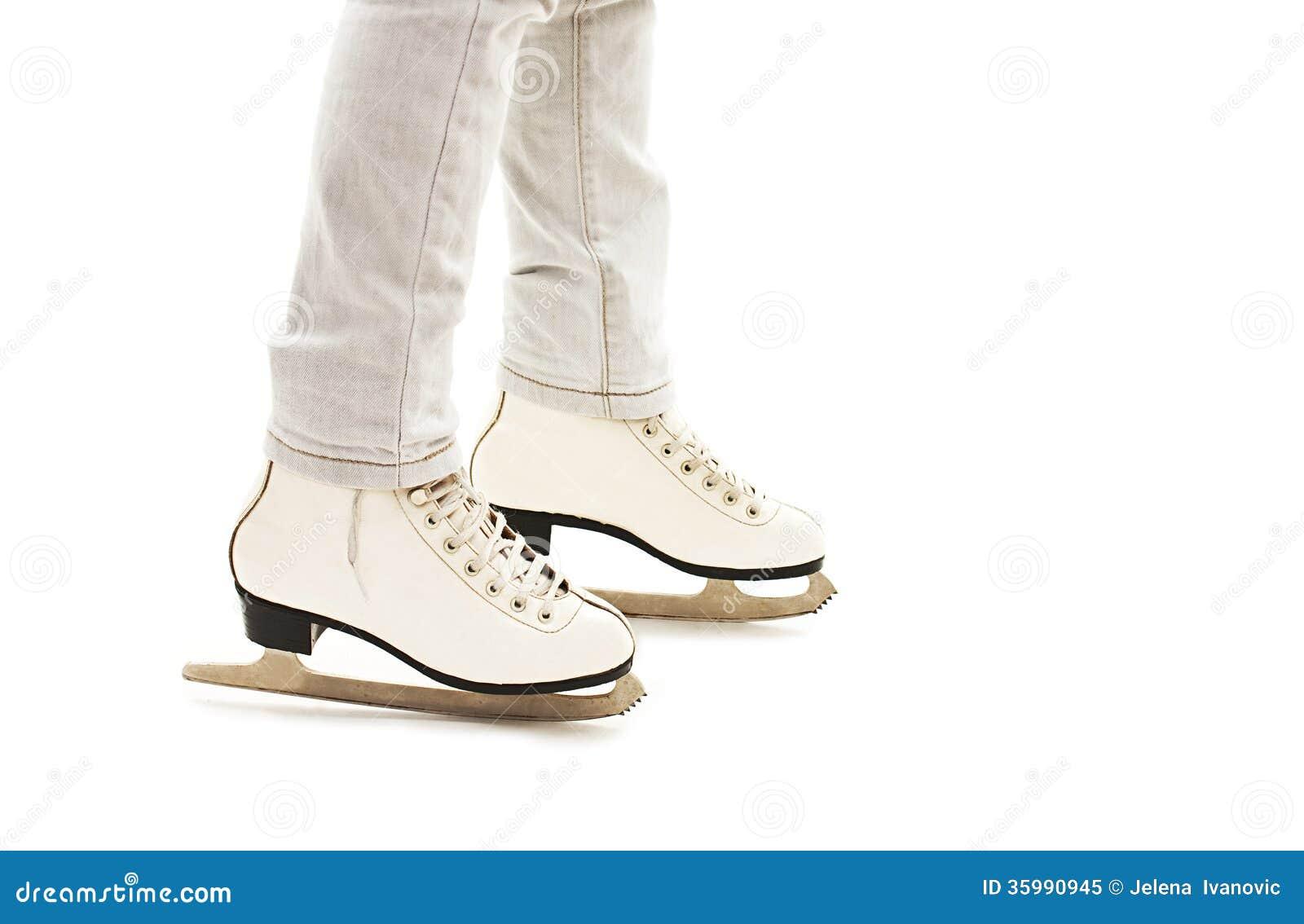 Os pés da menina nos patins de gelo brancos