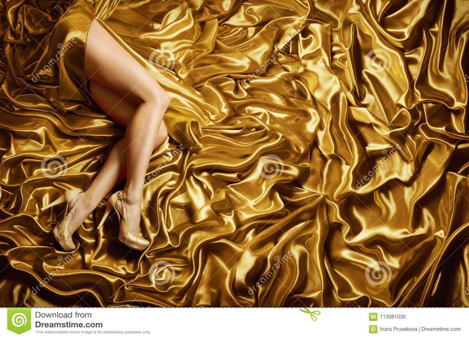 Os pés da mulher no fundo da tela de seda do ouro, formam sapatas douradas