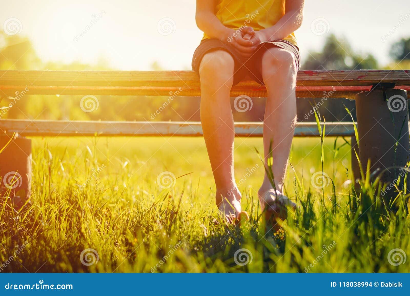 Os pés desencapados de um menino penduram para baixo de um banco