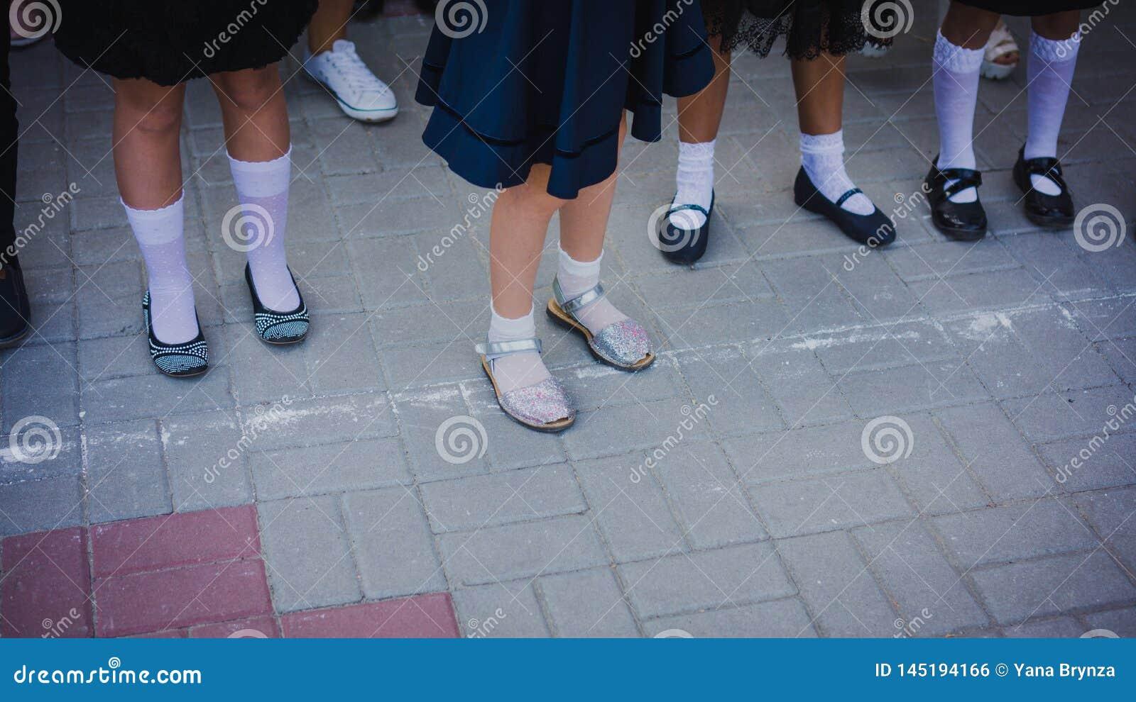 Os p?s do beb? no golfe branco e as sapatas bonitas est?o na forma??o na linha da escola o 1? de setembro 1? de setembro - linha