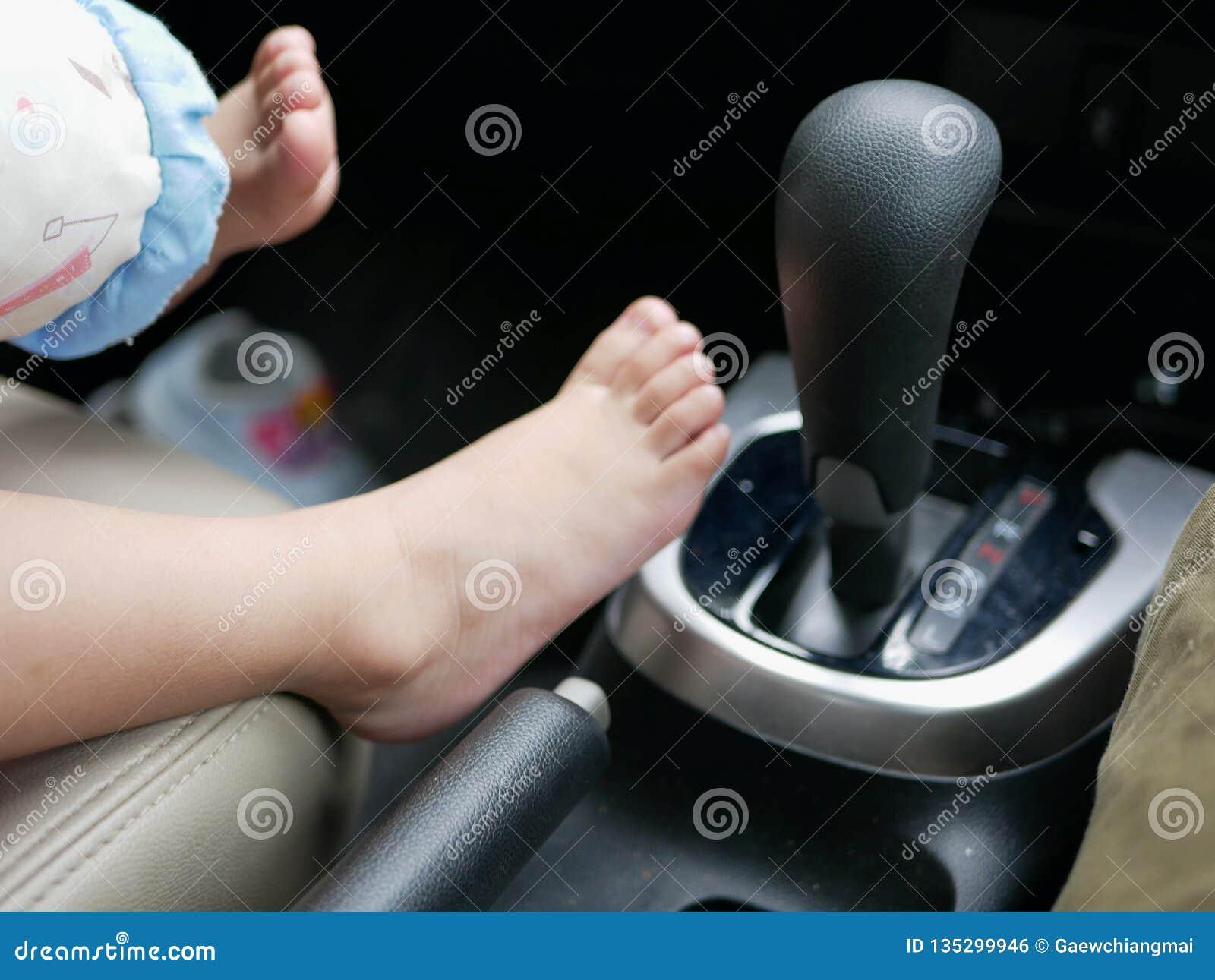 Os pés do bebê que estão sendo postos ao lado de uma engrenagem de um carro de condução