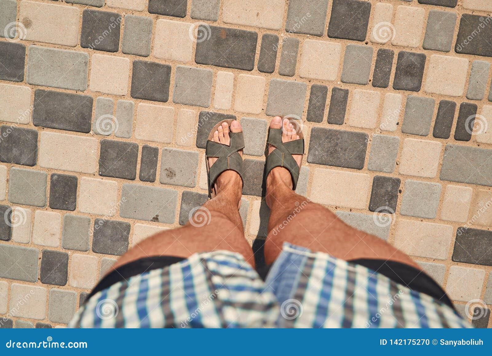 Os pés do homem em pavimentar a telha da opinião superior da primeira pessoa Olhar do verão