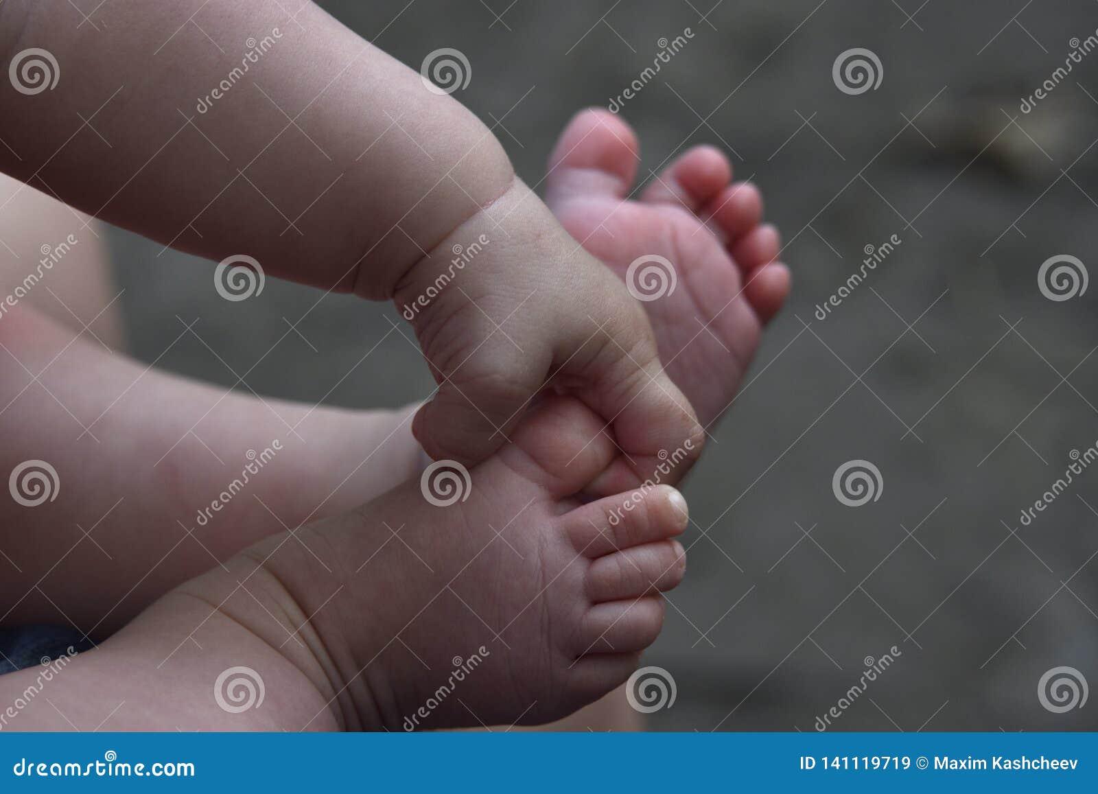 Os pés e os punhos do bebê fecham-se acima no fundo cinzento