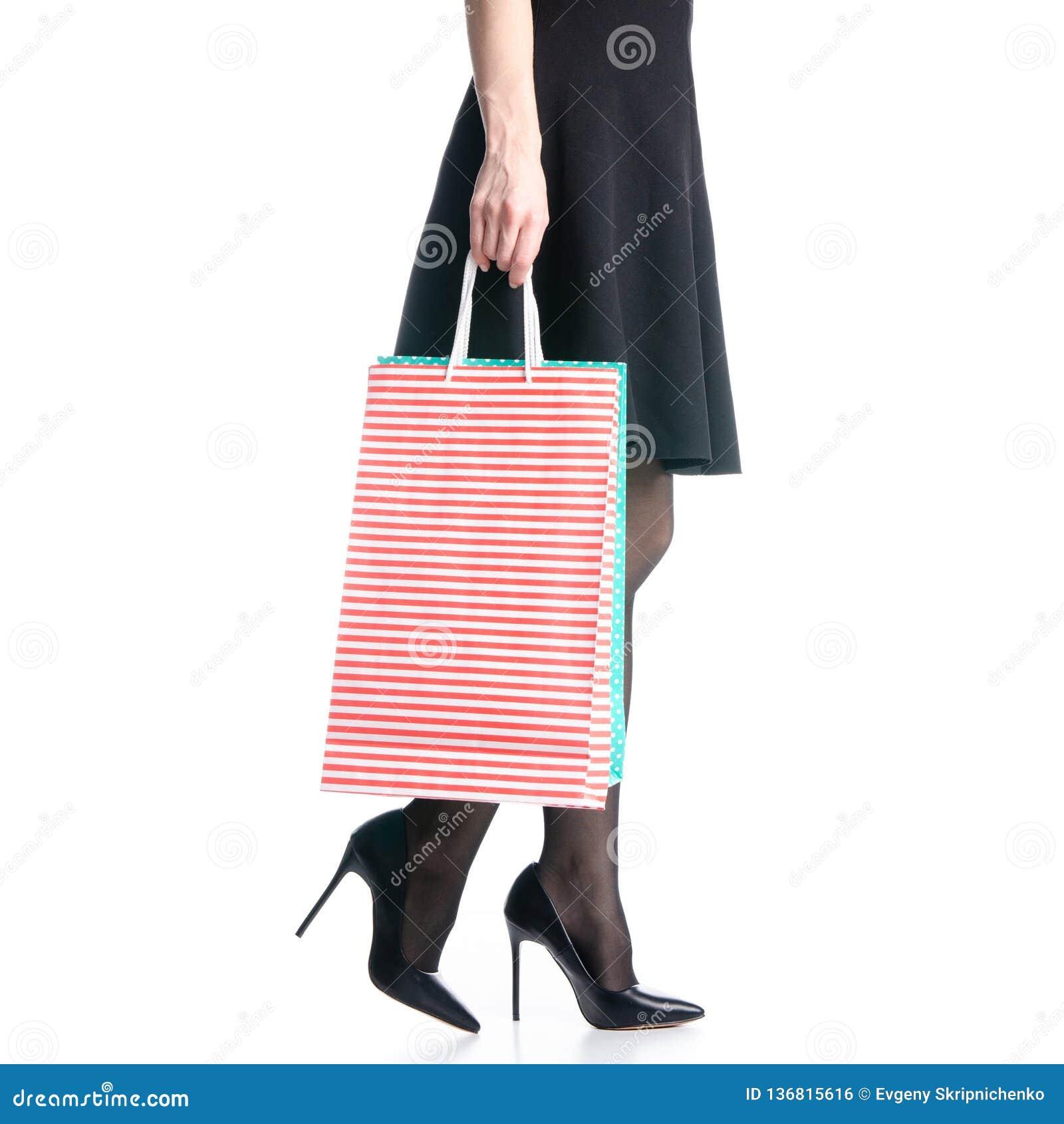 Os pés fêmeas em sacos pretos das sapatas dos saltos altos empacotam a forma preta da saia vão