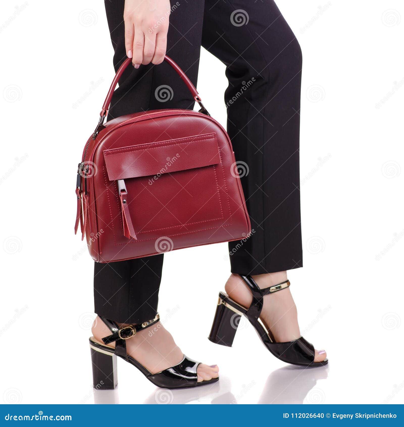 Os pés fêmeas no preto clássico arfam sapatas pretas da laca com a bolsa de couro vermelha à disposição