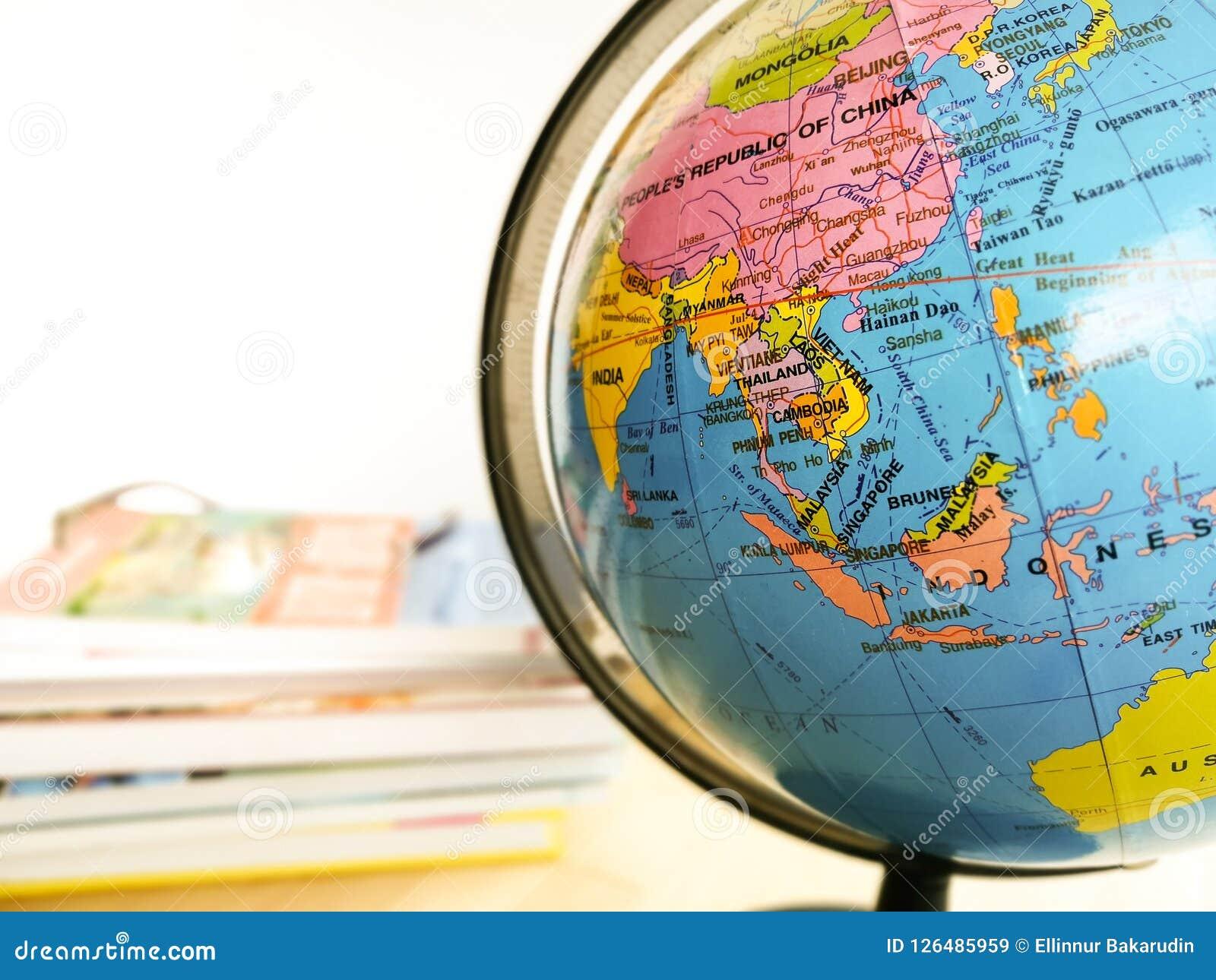 Os países e os continentes fecham-se acima com o mapa de cor em um globo com os livros no fundo Imagens de Stock Royalty Free