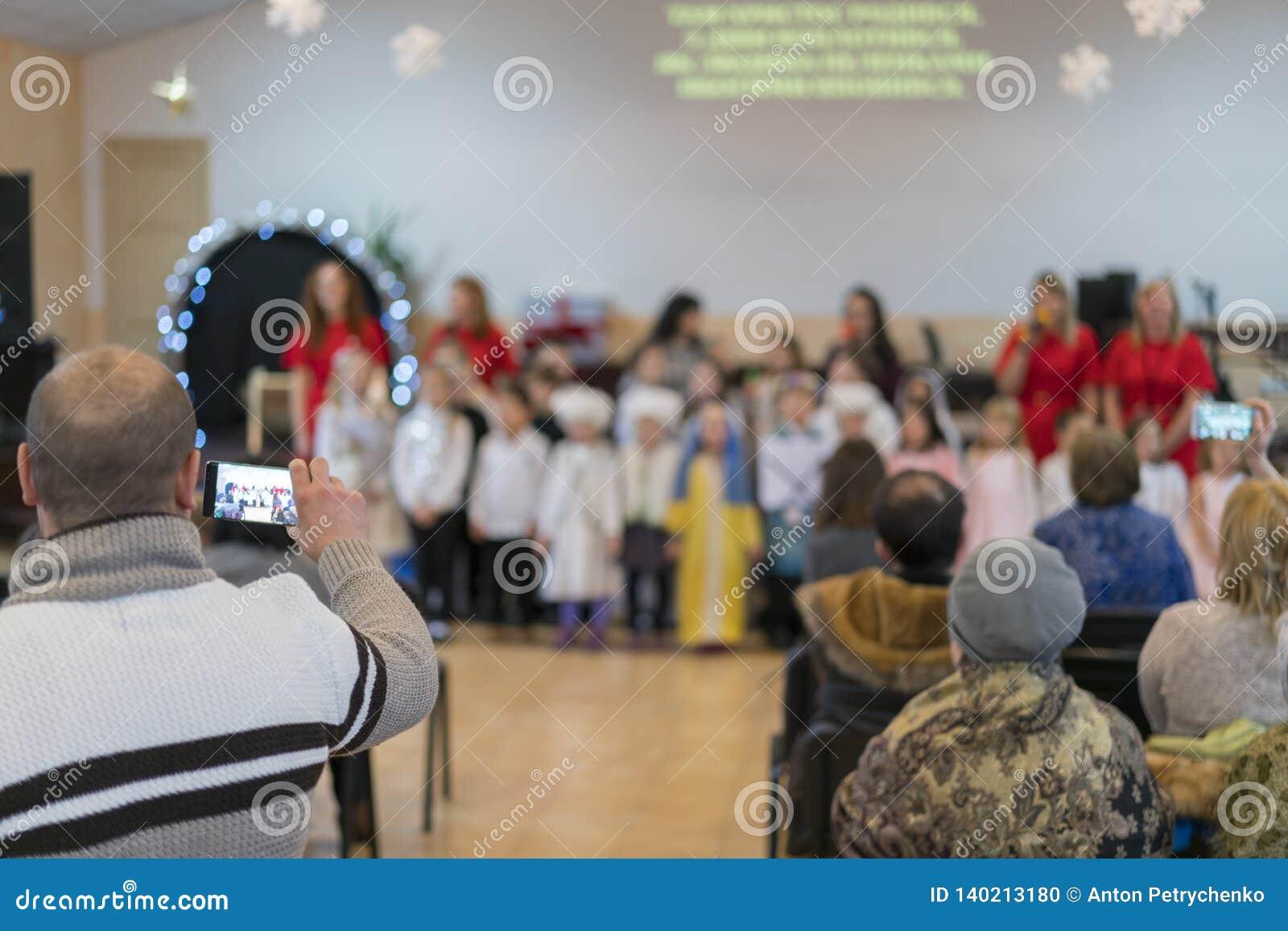 Os pais estão olhando as crianças do desempenho no jardim de infância Um feriado das crianças no jardim de infância blurry
