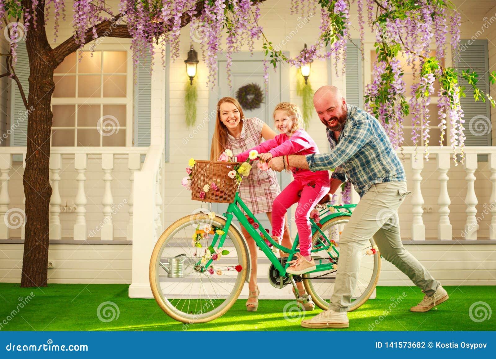Os pais felizes com uma criança, filha, aprendem montar em casa uma bicicleta, férias de verão do estilo de vida da família