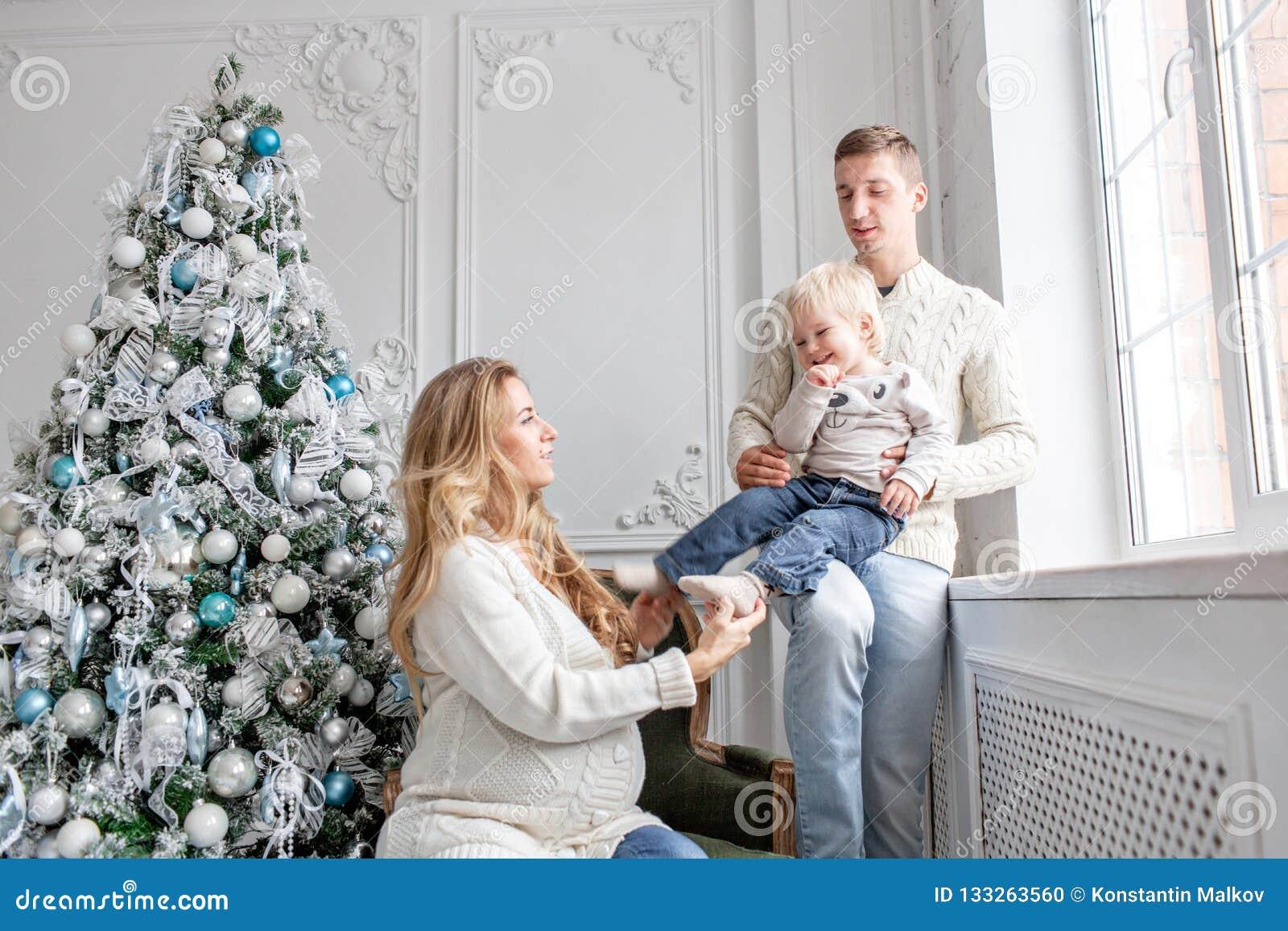 Os pais novos enganam ao redor e jogam com pouco filho Família feliz que tem o divertimento em casa Manhã de Natal na vida brilha