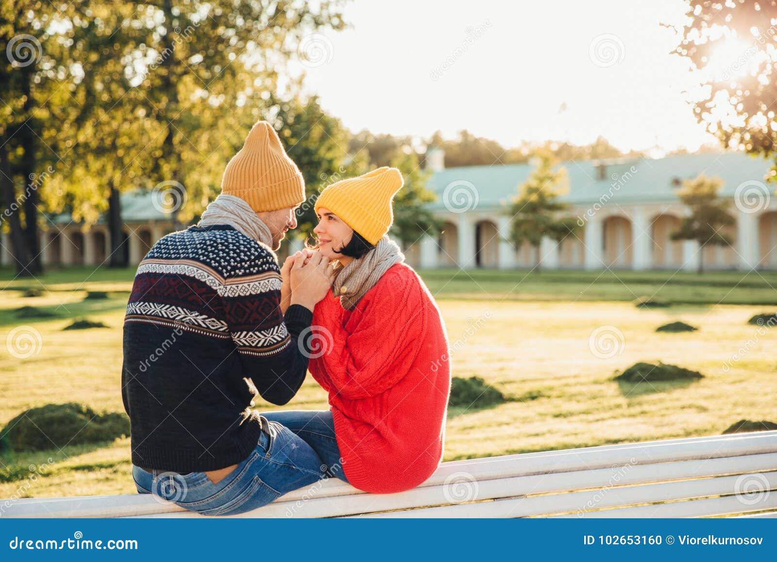 Os pares adoráveis passam o tempo junto: a posse atrativa do homem suas mãos do ` s da amiga, indo fazer sua proposta, olha com g
