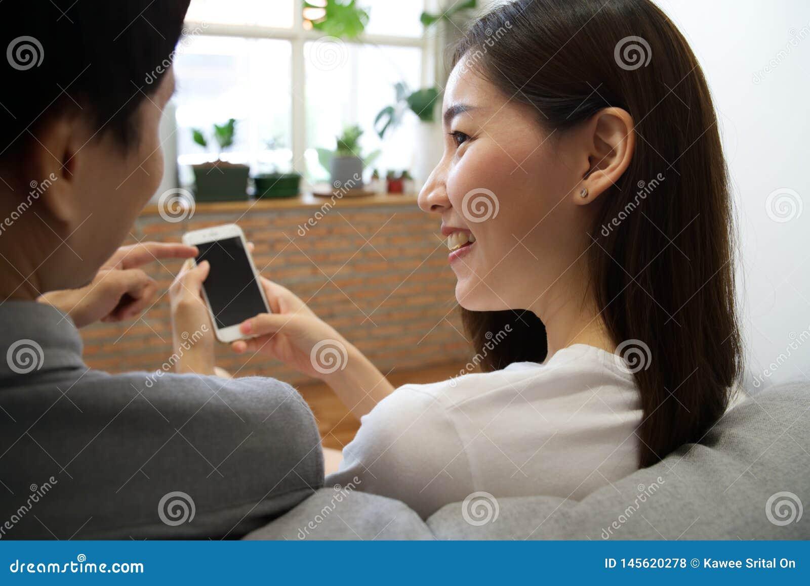 Os pares asiáticos novos que sentam-se no sofá estão olhando o telefone celular