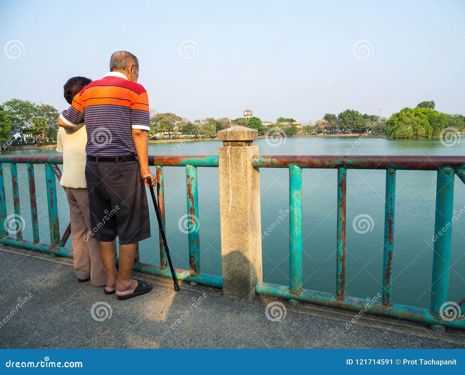 Os pares asiáticos superiores românticos felizes estão na ponte na frente do lago O marido está com sua esposa Conceito do coupl