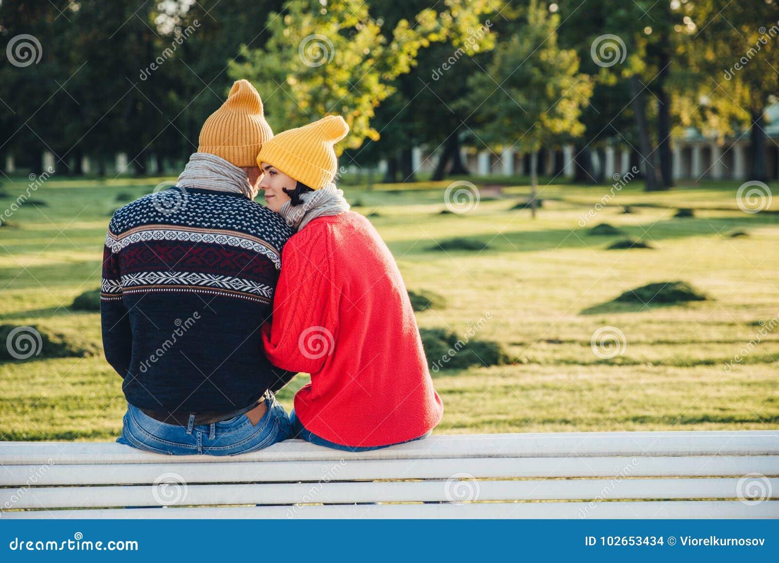 Os pares bonitos sentam-se no banco junto, vestem a roupa morna e os chapéus feitos malha, abraçam-se, o amor expresso e o bom re