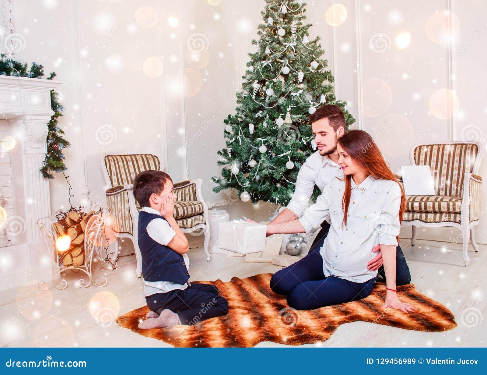 Os pares felizes da família dão presentes na sala de visitas, atrás da árvore de Natal decorada, a luz para dar uma atmosfera aco