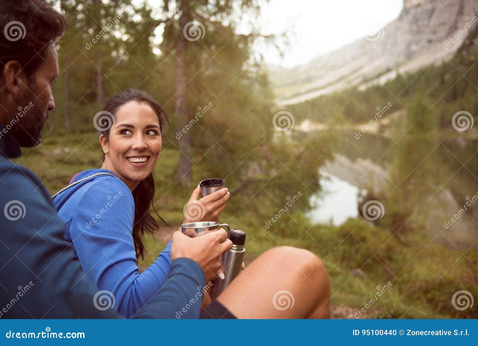 Os pares felizes de sorriso do homem e da mulher apreciam a opinião do panorama do lago com luz do alargamento do sol Grupo de ve
