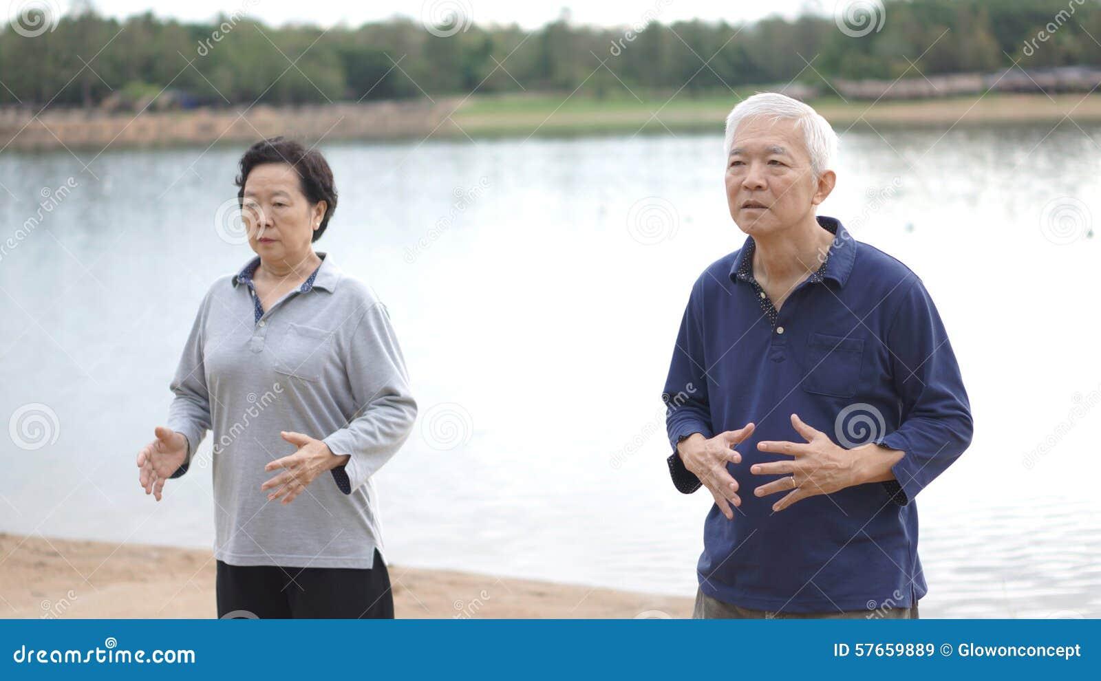 Os pares idosos superiores asiáticos praticam Taichi, ne do exercício do gongo de Qi
