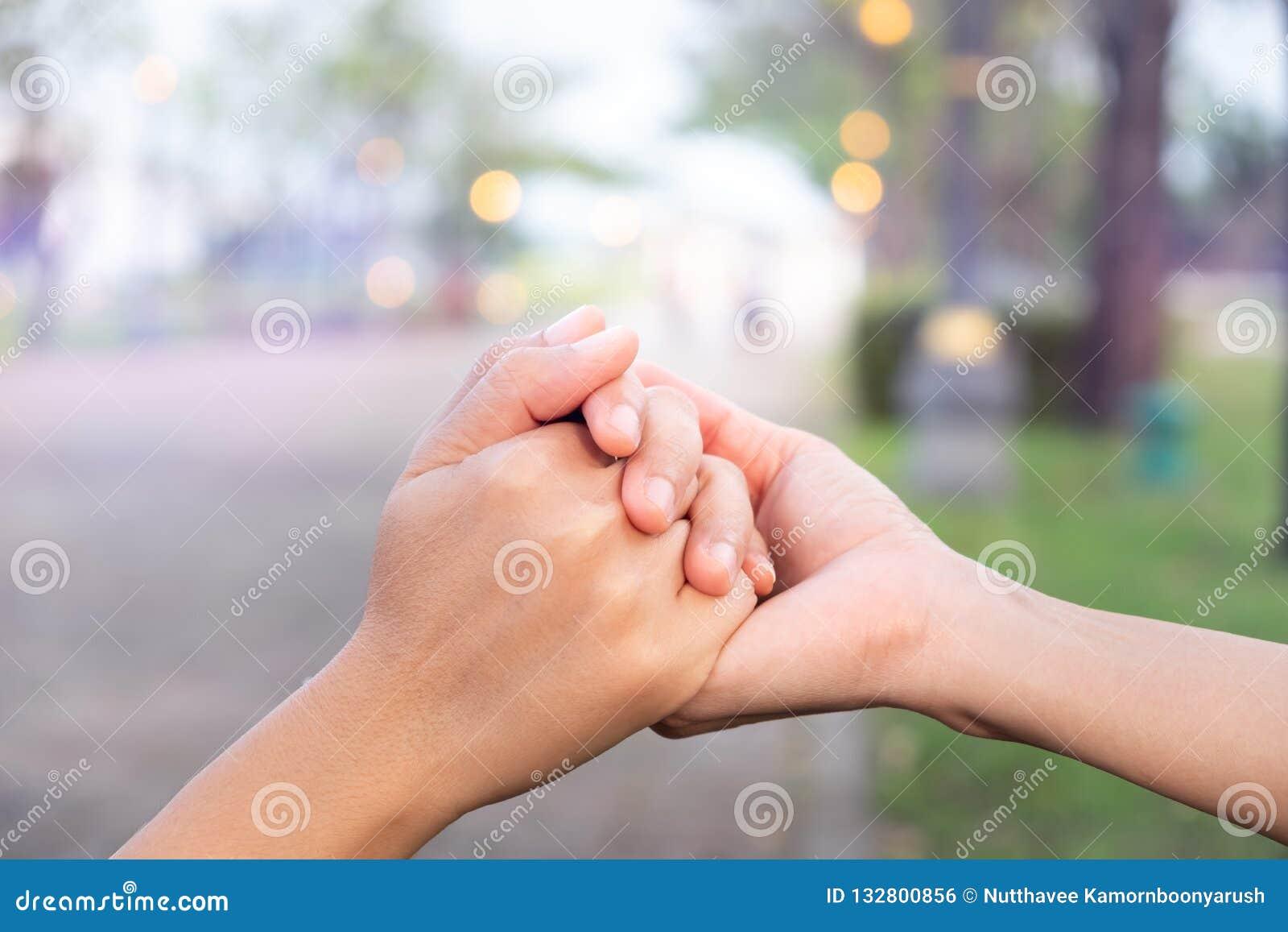 Os pares mantêm as mãos unidas no jardim do amor