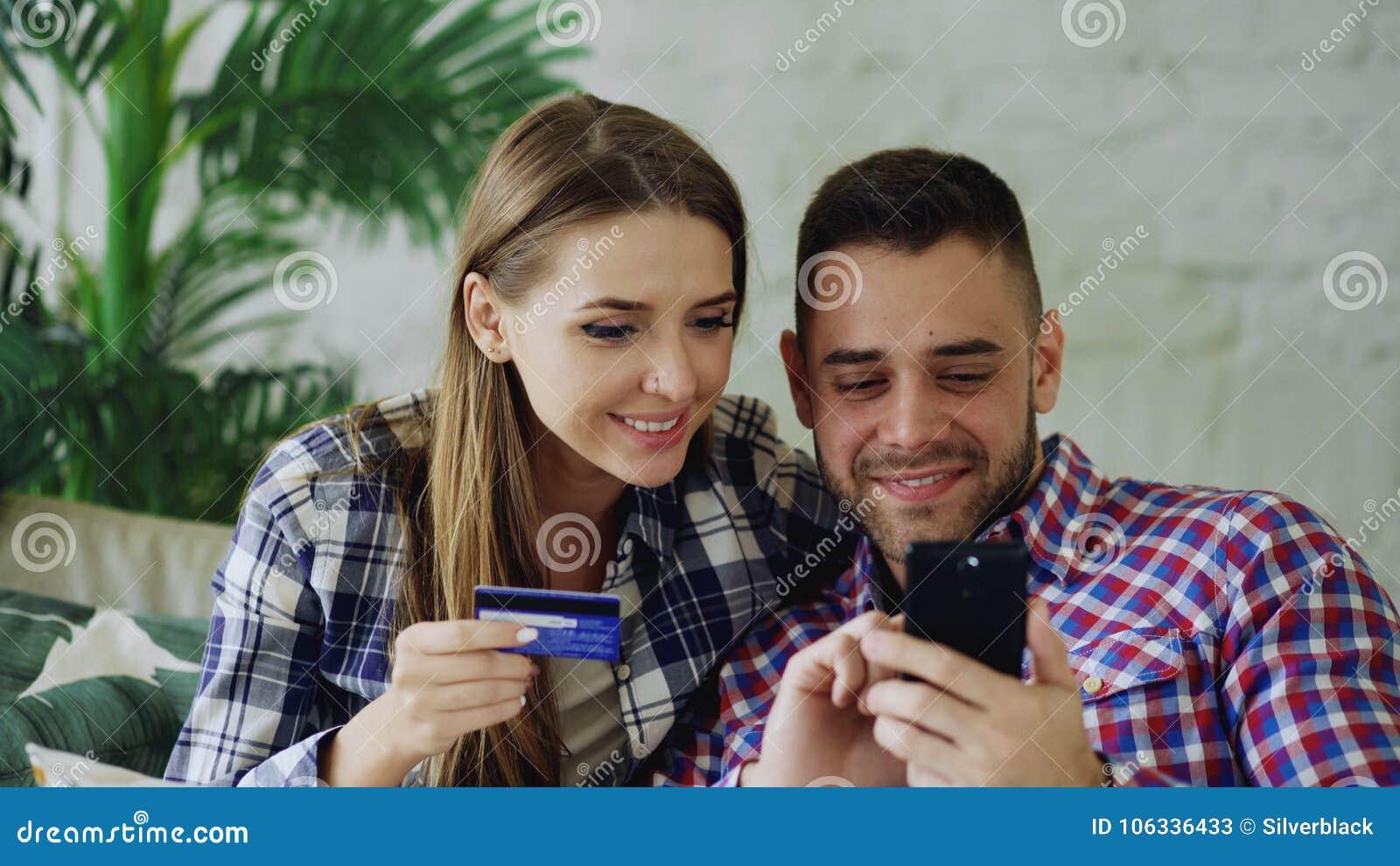 Os pares novos atrativos com smartphone e a compra do cartão de crédito no Internet sentam-se no sofá na sala de visitas em casa