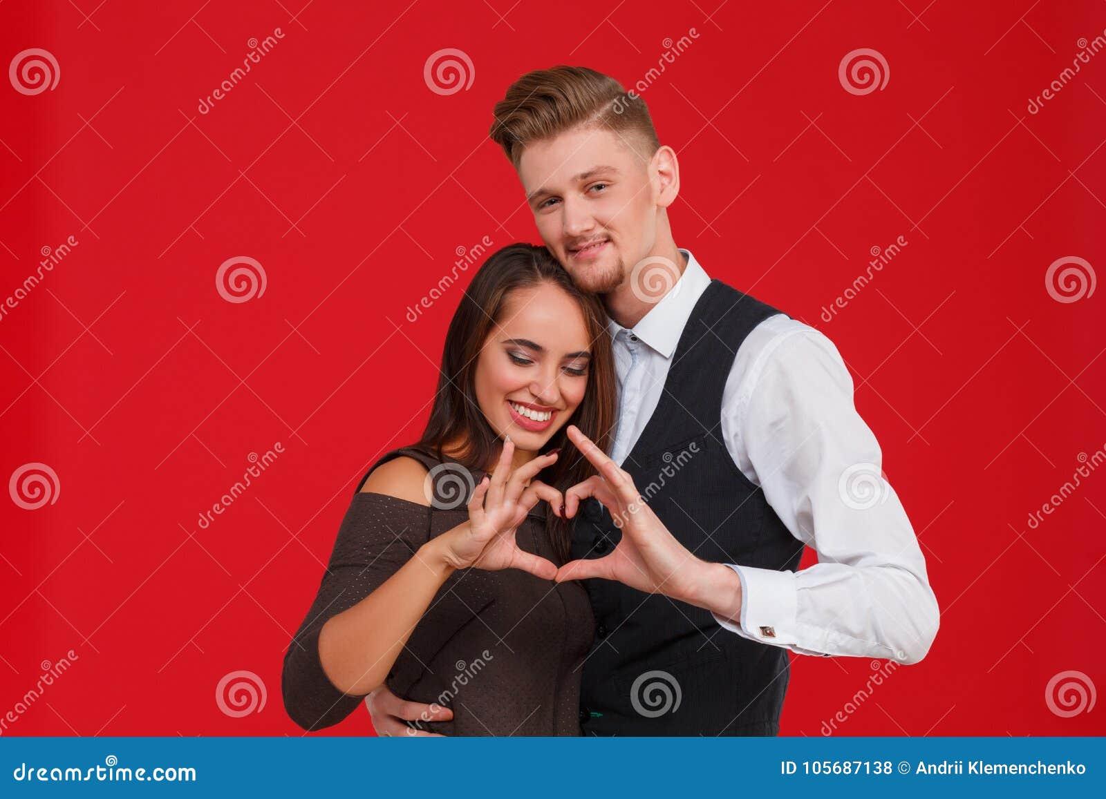 Os pares novos e bonitos no amor fazem um coração em um fundo vermelho O conceito do dia do ` s do Valentim