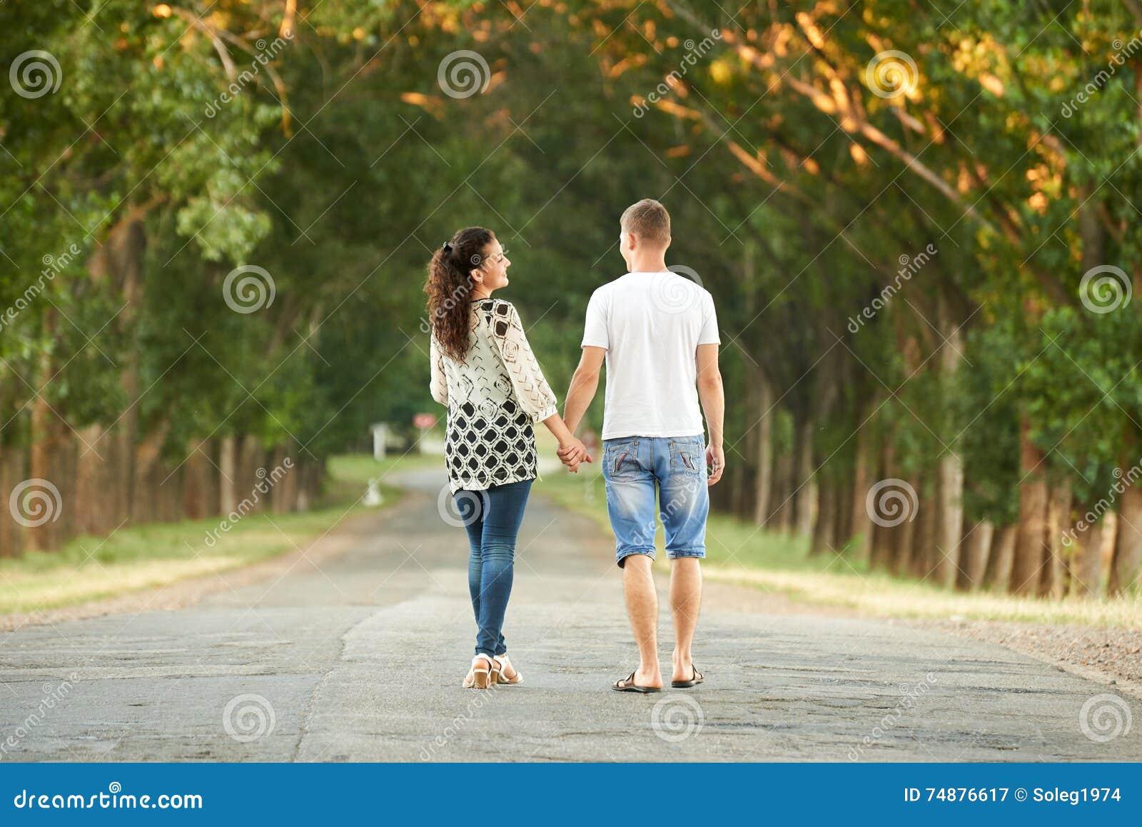 Os pares novos felizes andam na estrada secundária exterior, conceito romântico dos povos, temporada de verão