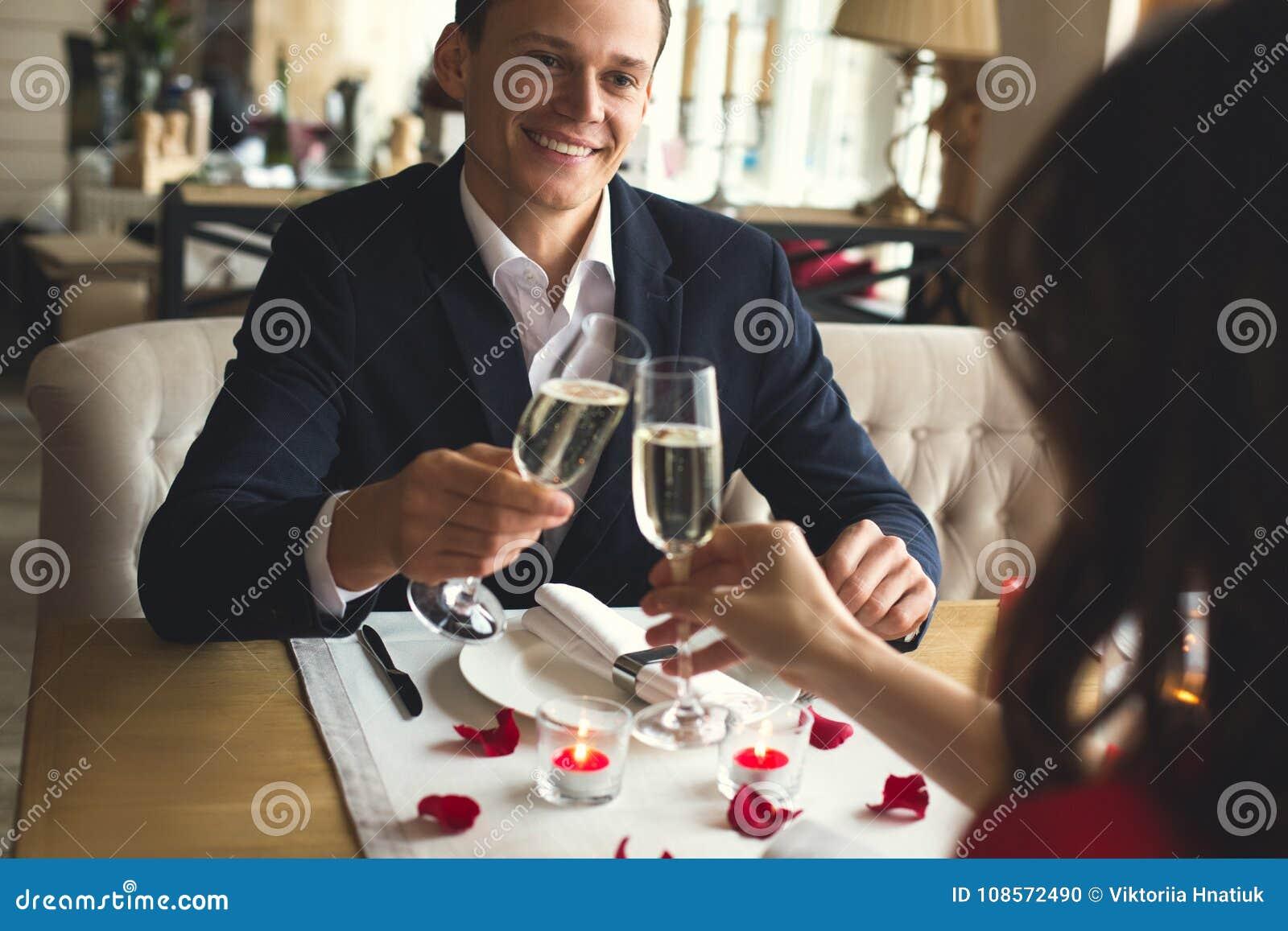 Os pares novos que têm o jantar romântico nos elogios bebendo do champanhe do restaurante filtram