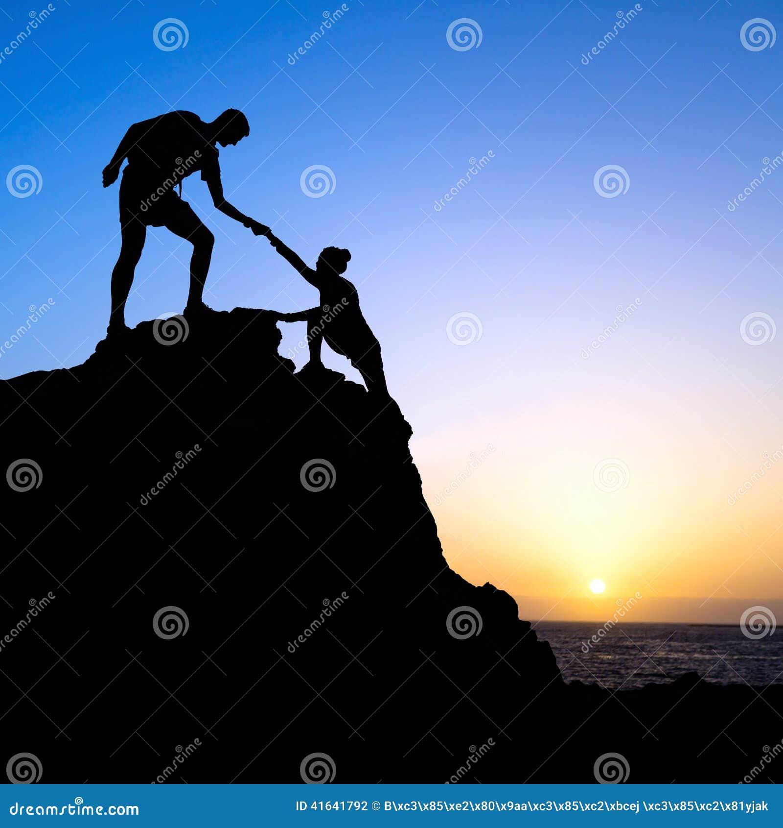 Os pares, o homem e a mulher ajudam a silhueta nas montanhas