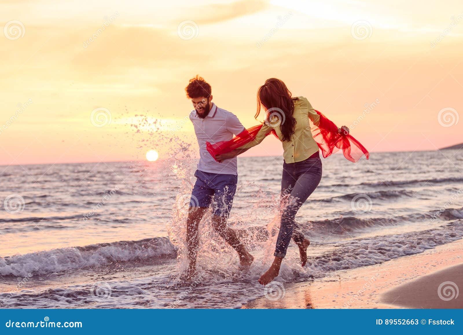 Os pares românticos novos felizes no amor têm o divertimento na praia bonita no dia de verão bonito