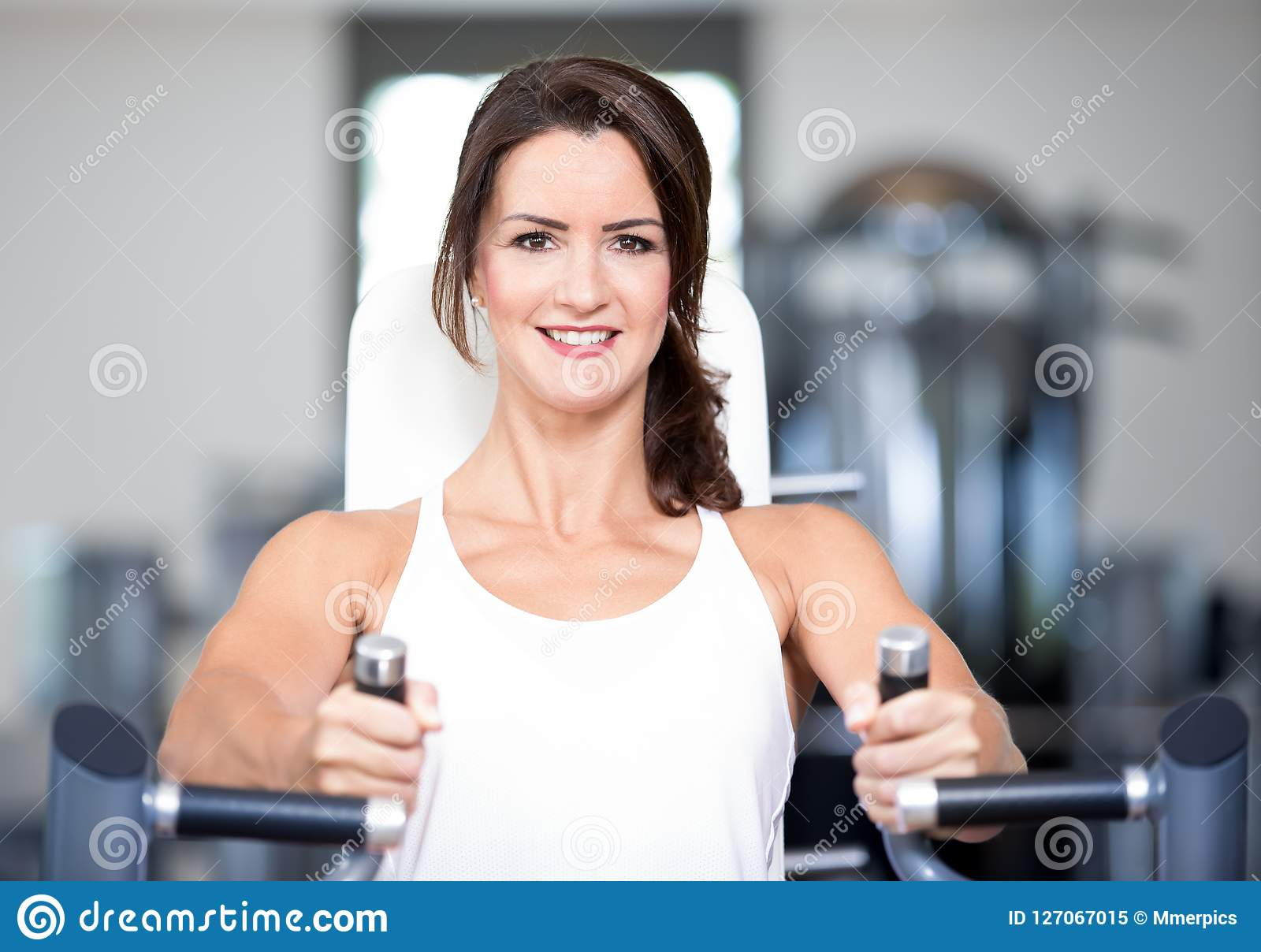 Os pares  sexy  bonitos do homem da mulher estão fazendo um exercício no gym dos fitnes - imprensa da caixa, banco