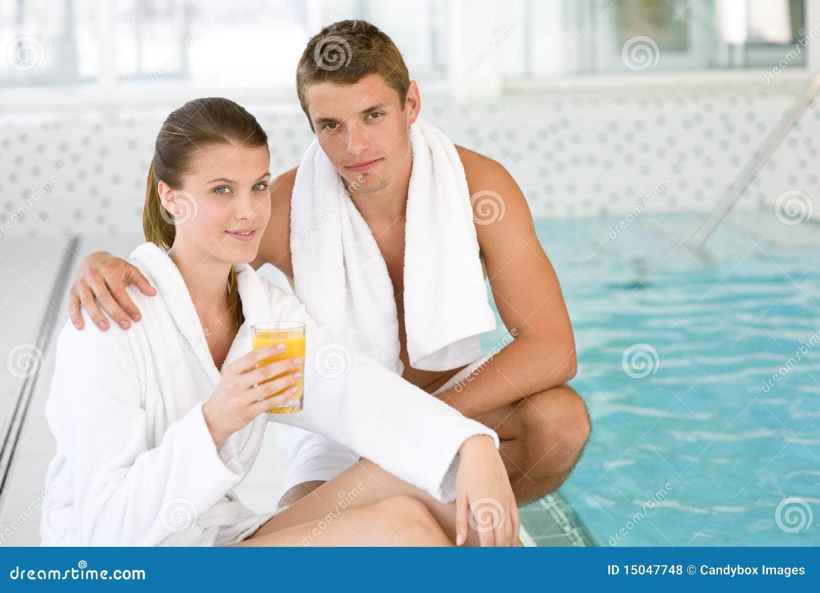 Os pares sportive novos relaxam na piscina