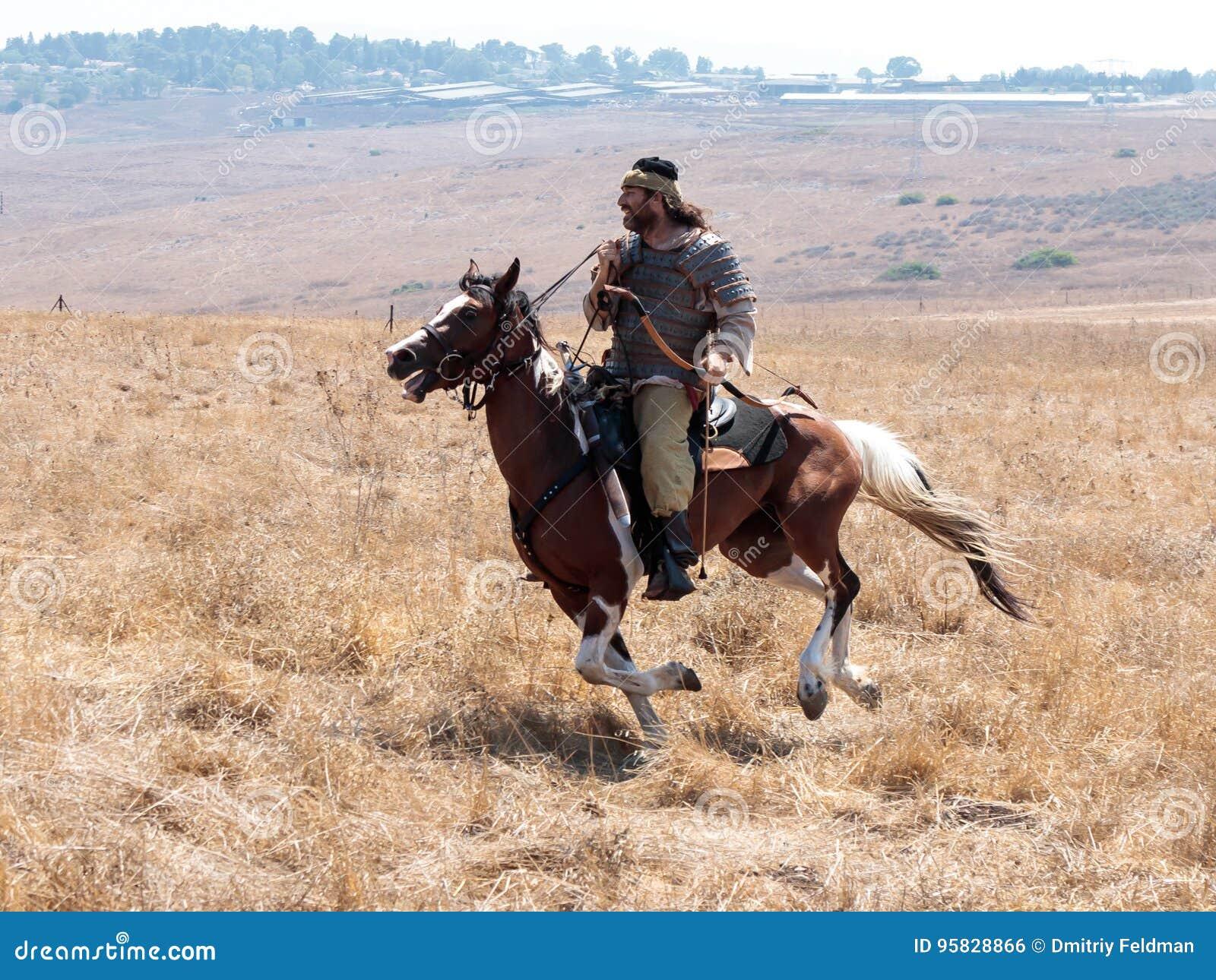 Os participantes na reconstrução dos chifres de Hattin lutam em 1187 movendo ao redor o campo de batalha perto de Tiberias, Israe