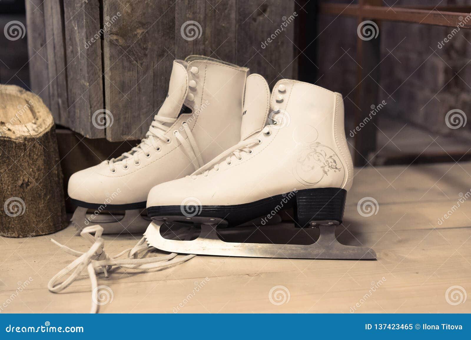 Os patins brancos das mulheres estão no assoalho feminine para patinar Esporte de inverno