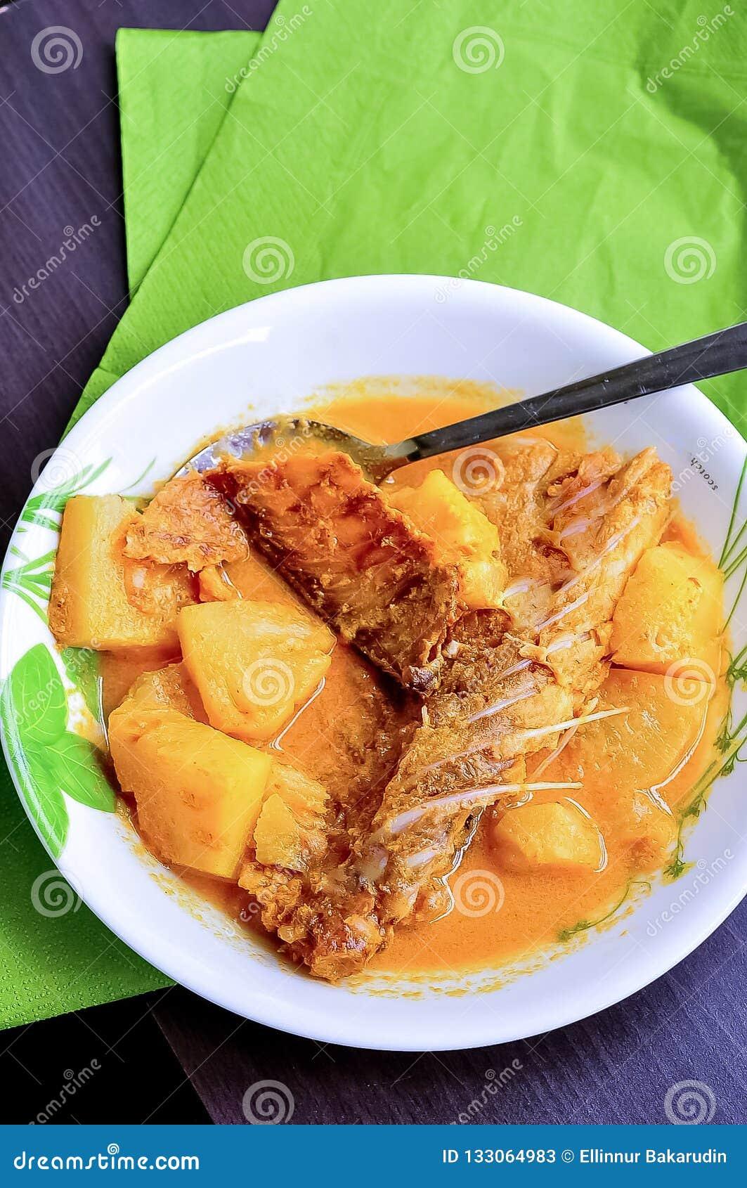 OS PEIXES de GULAI IKAN KERING/DRIED SURRAM/BOUILLABAISSES SALGADOS - o prato tradicional malaio serviu em uma placa branca