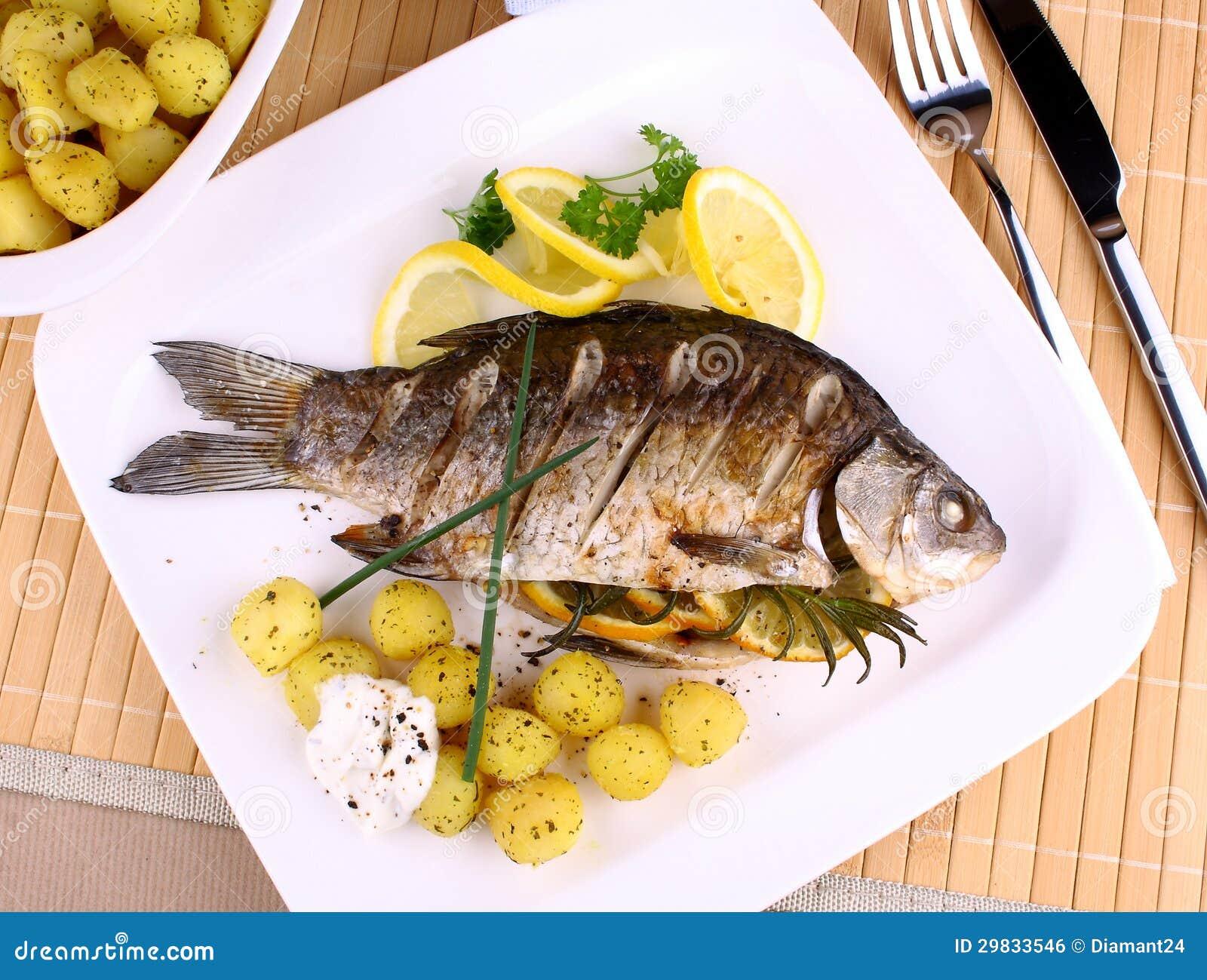Os peixes grelhados seriram com batatas, limão e molho
