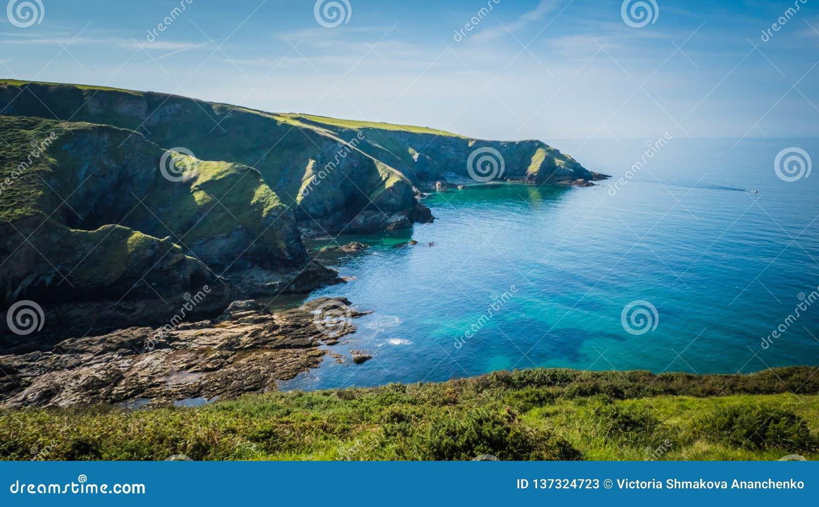 Os penhascos verdes bonitos ajardinam pelo Oceano Atlântico azul perto do cargo Isaac em Cornualha, Reino Unido