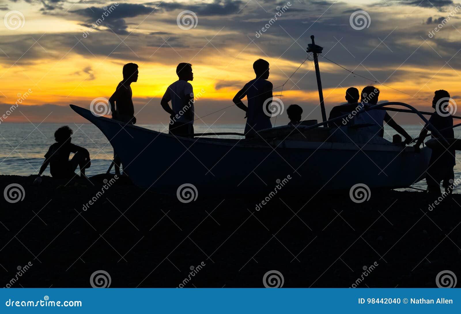 Os pescadores mostram em silhueta na praia filipino
