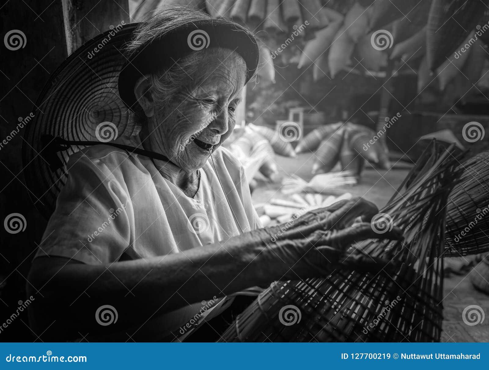 Os pescadores vietnamianos estão fazendo a cestaria para o equipamento de pesca em