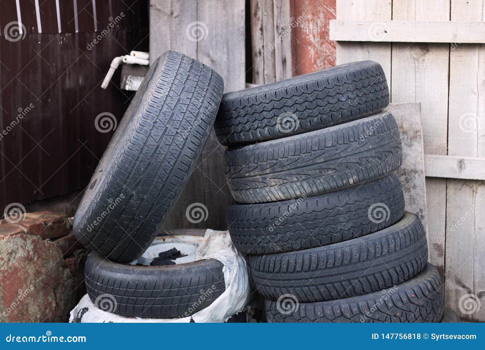 Os pneus de borracha velhos encontram-se aleatoriamente perto de uma casa de madeira abandonada